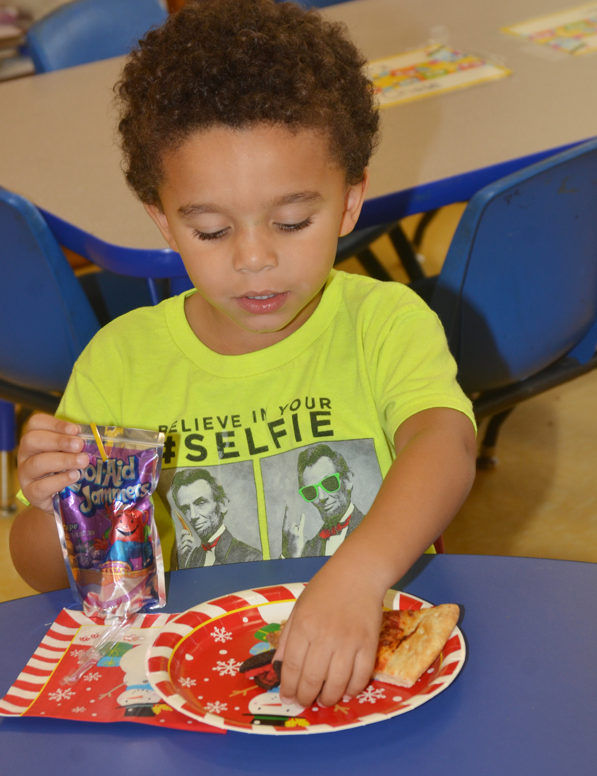 CES preschool student Tyrek Moore enjoys his cookies and pizza.