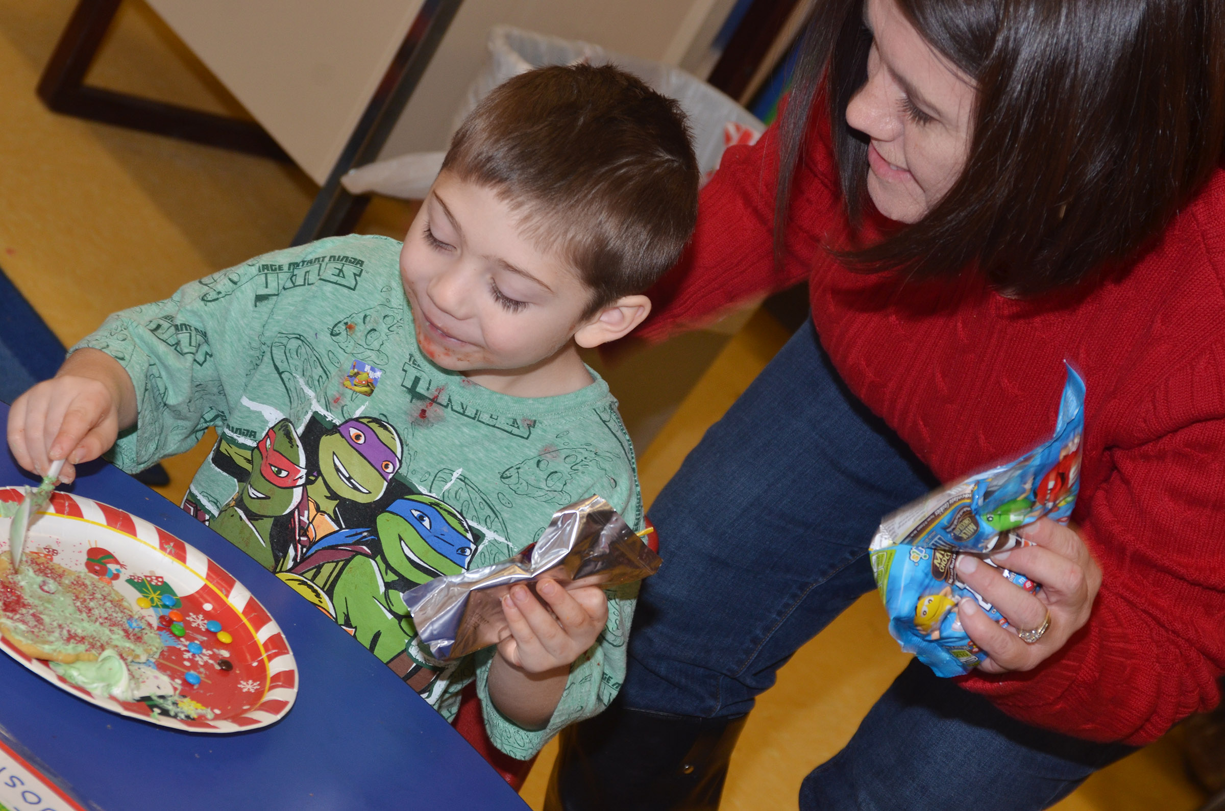 CES preschool teacher Denise Spencer helps Josiah Dean decorate his cookie.