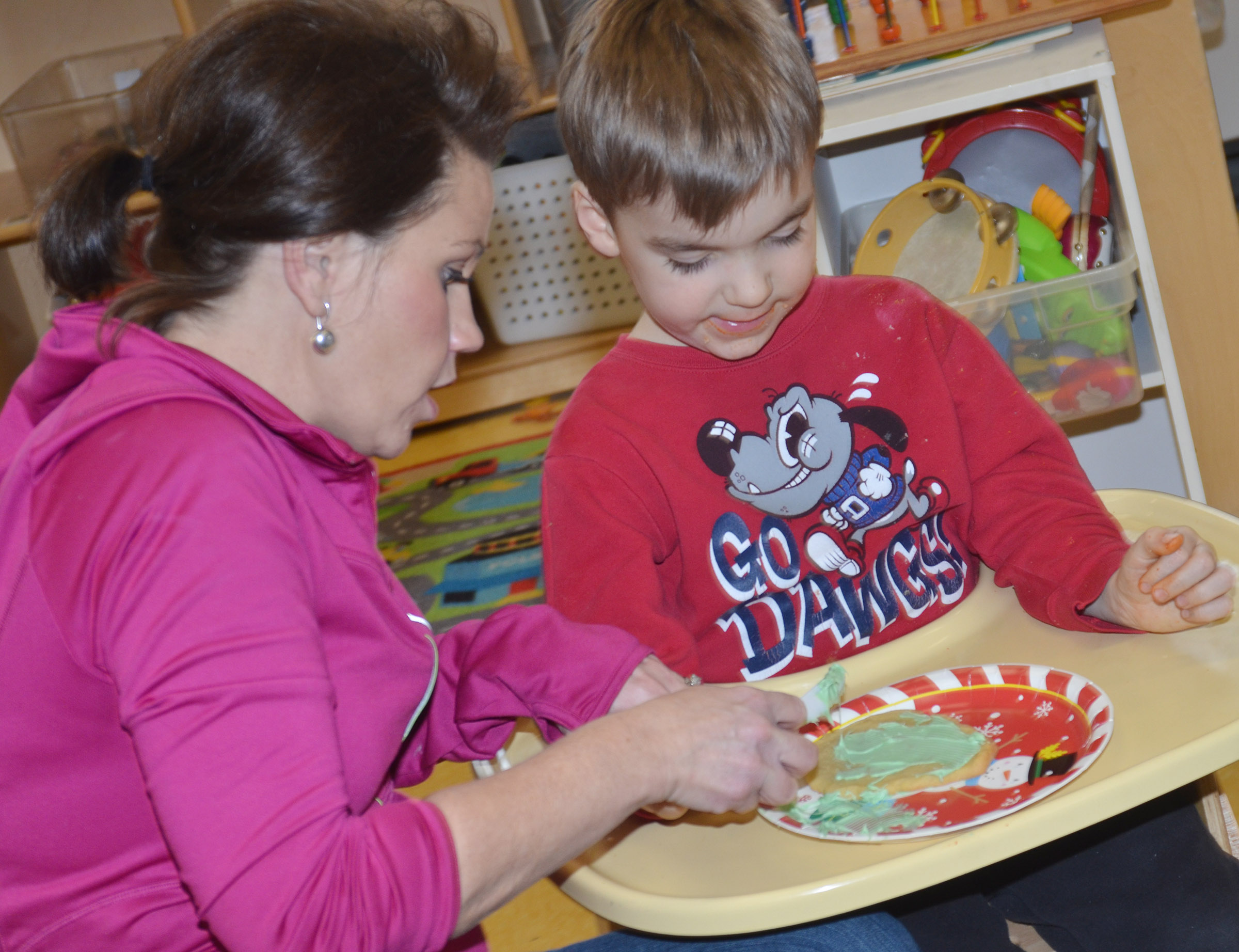 CES preschool assistant Beth Sandidge helps Finley Williams decorate his cookie.