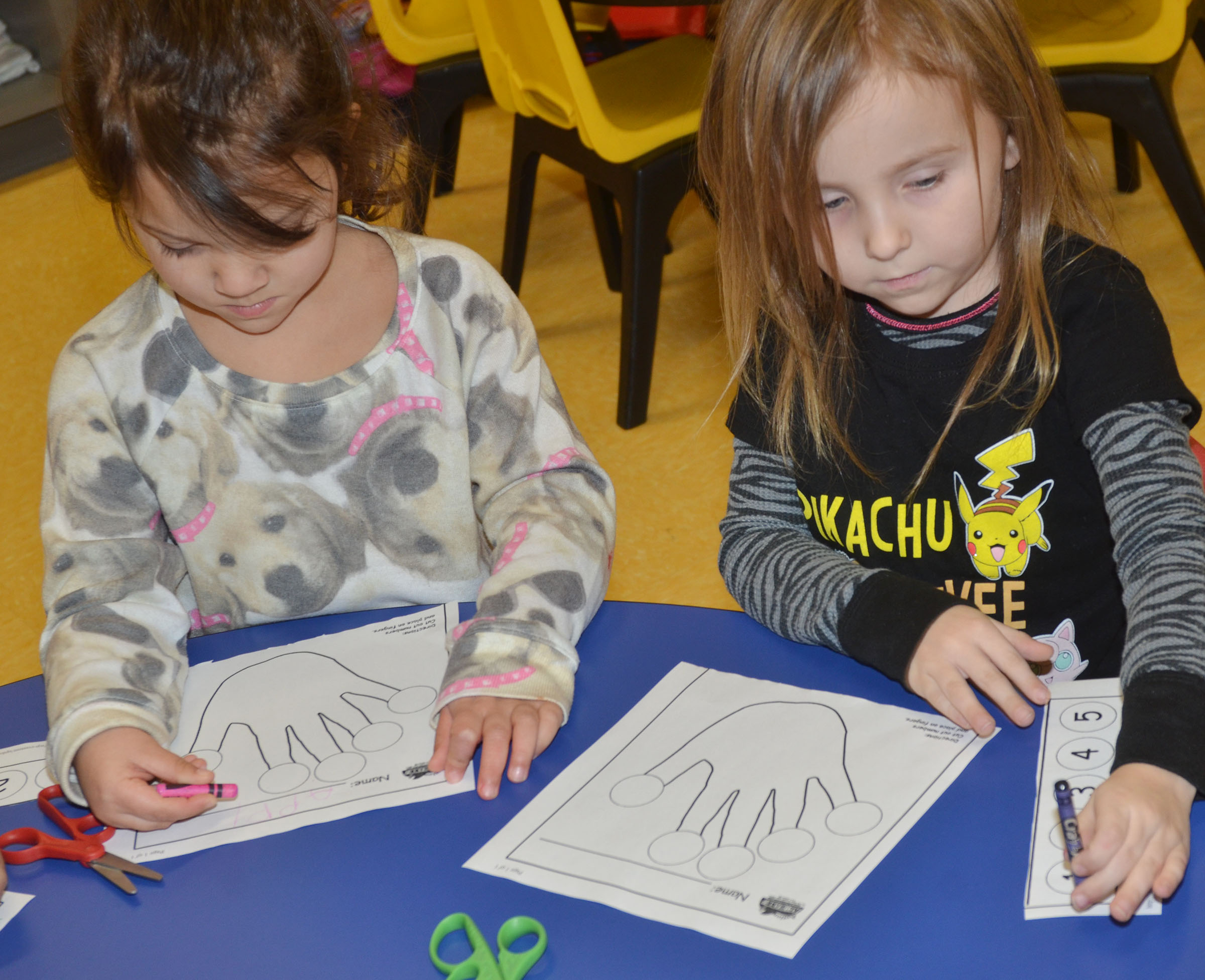 CES preschool students Addisyn Taylor, at left, and Tabitha Leggett color their hands.