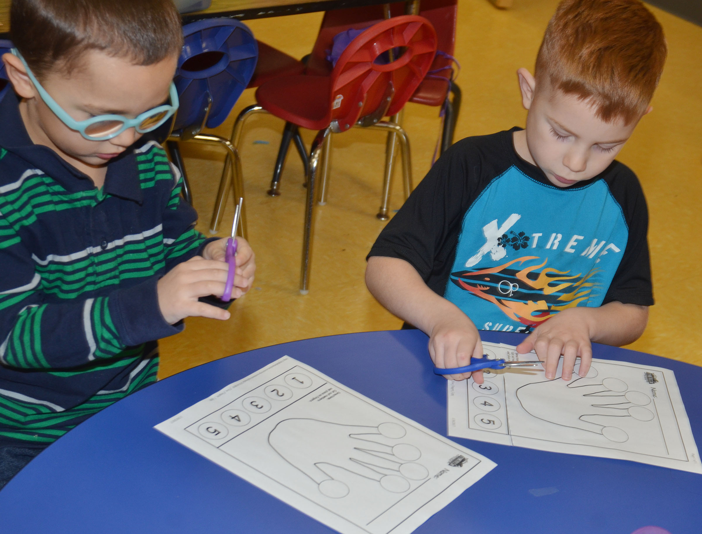 CES preschool students Chanler Mann, at left, and Kennon Dotson cut out their hands.