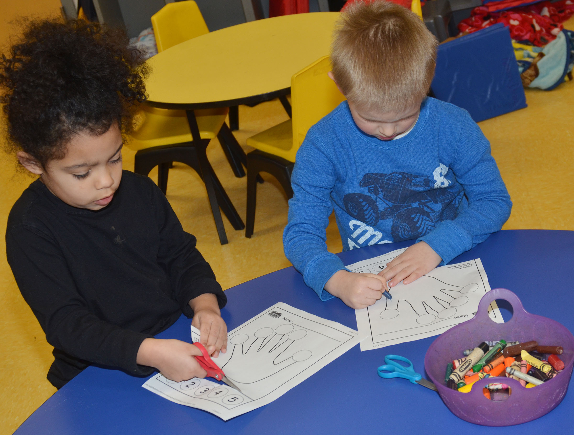 CES preschool students Rylee Karr, at left, and Jacob Parrish color and cut out their hands.