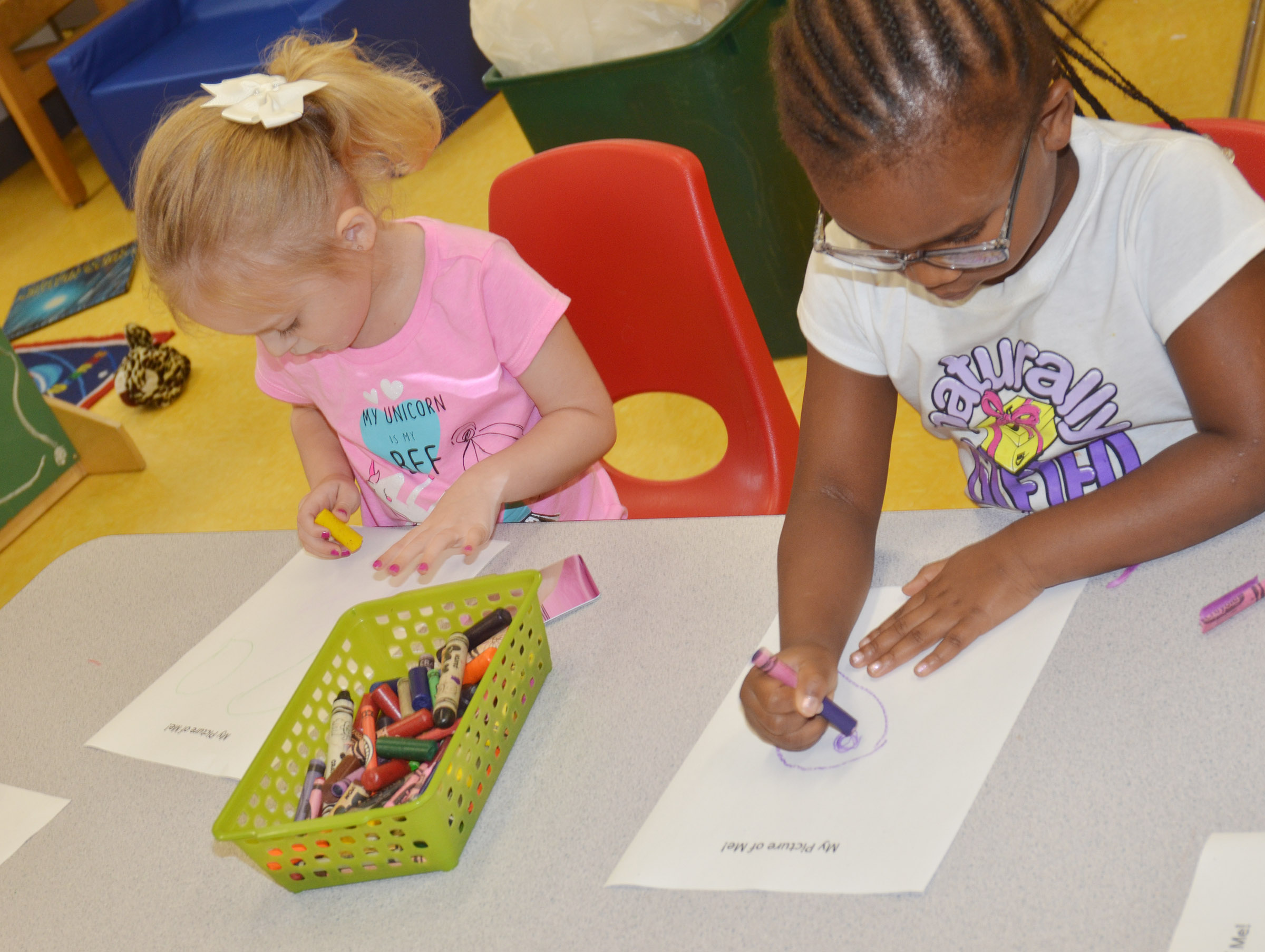 CES preschool students Kylie Thompson, at left, and Kyona Mitchell draw pictures of themselves.