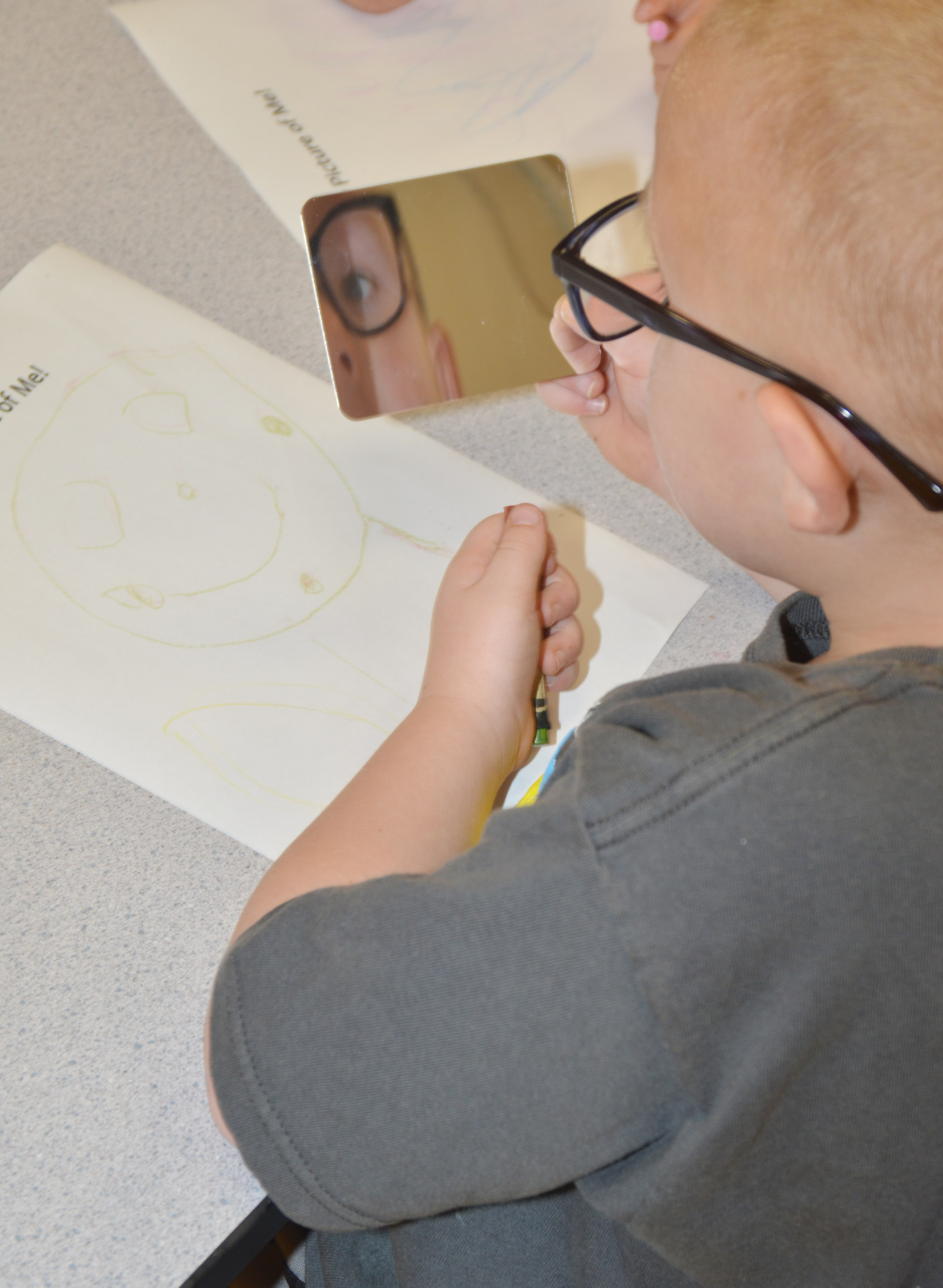 CES preschool student Anthony McClure looks at himself in the mirror as he draws a self-portrait.