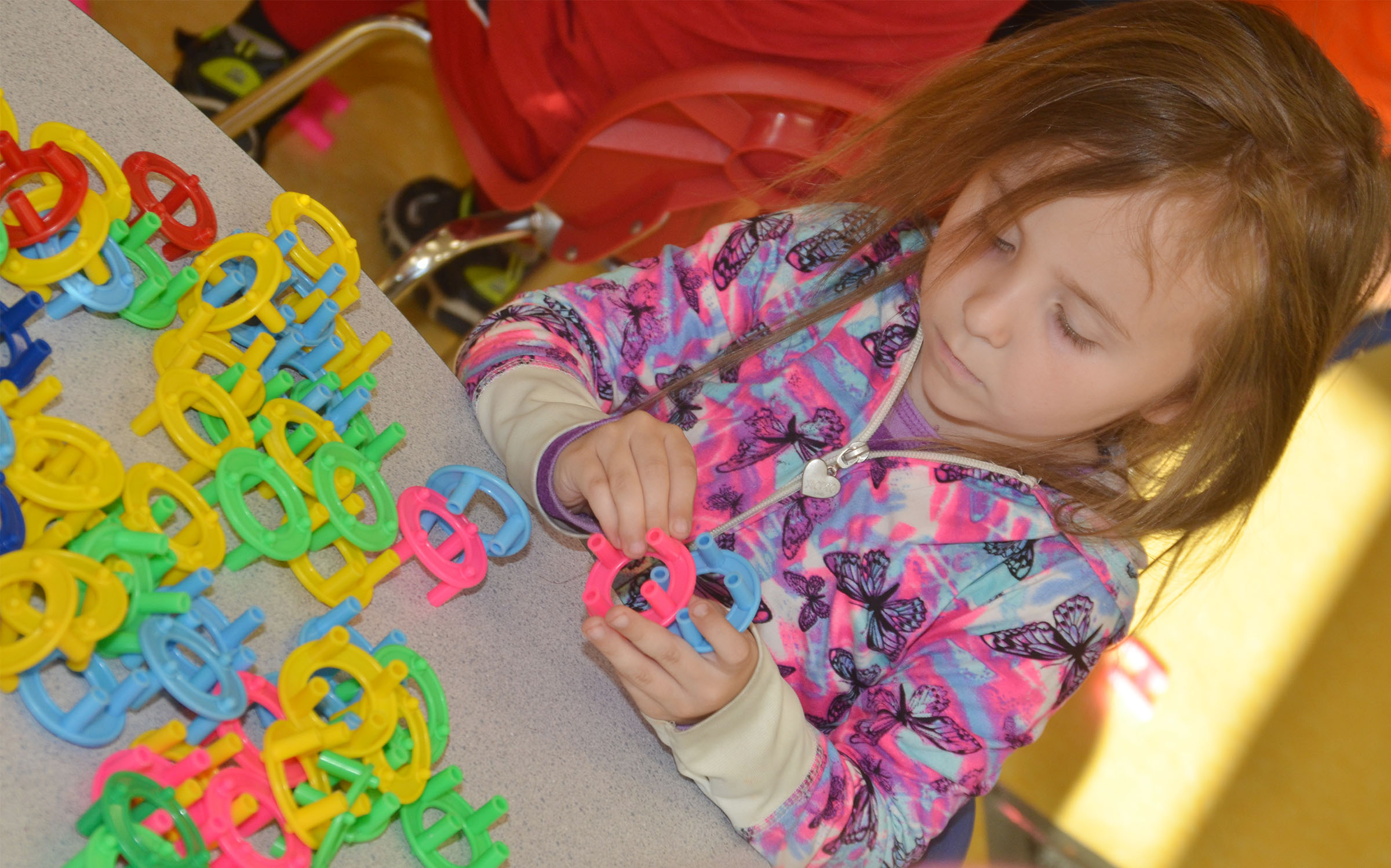 CES preschool student Tabitha Leggett builds.