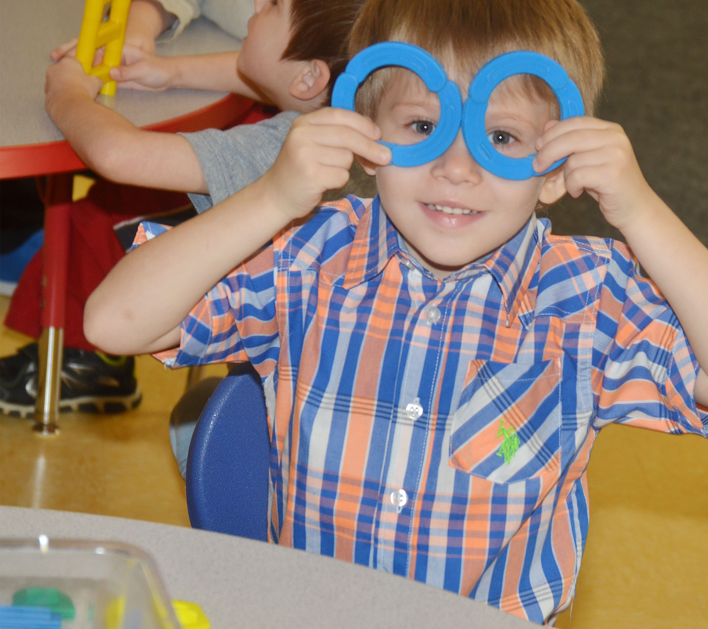 CES preschool student Elijah Russell makes glasses out of his building blocks.