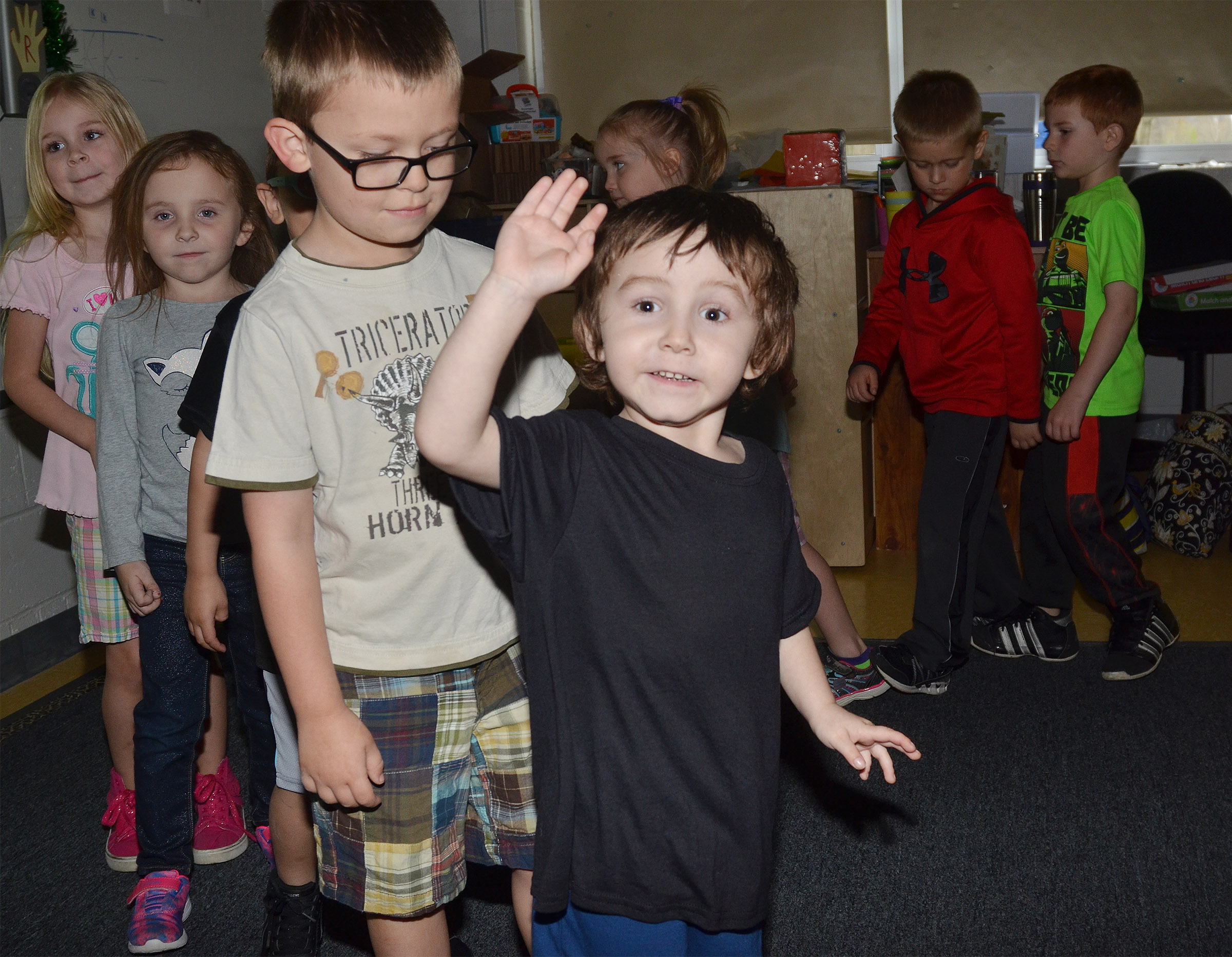 CES preschool student Noelan McMahan waves hello to his preschool teacher, Sherry Cowherd, as he dances with his classmates.