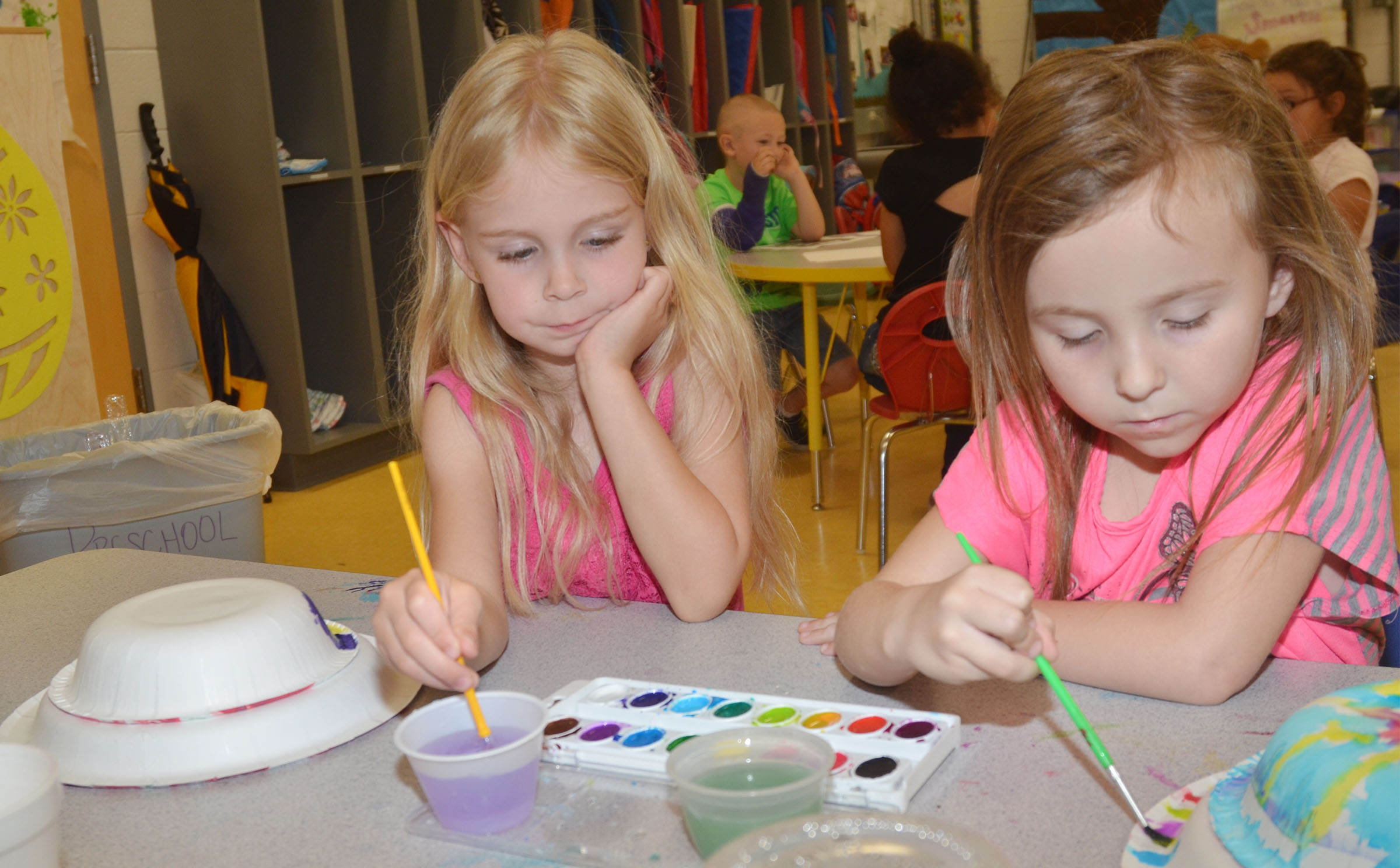 CES preschool students Alinna Bray, at left, and Tabitha Leggett paint their Derby hats.