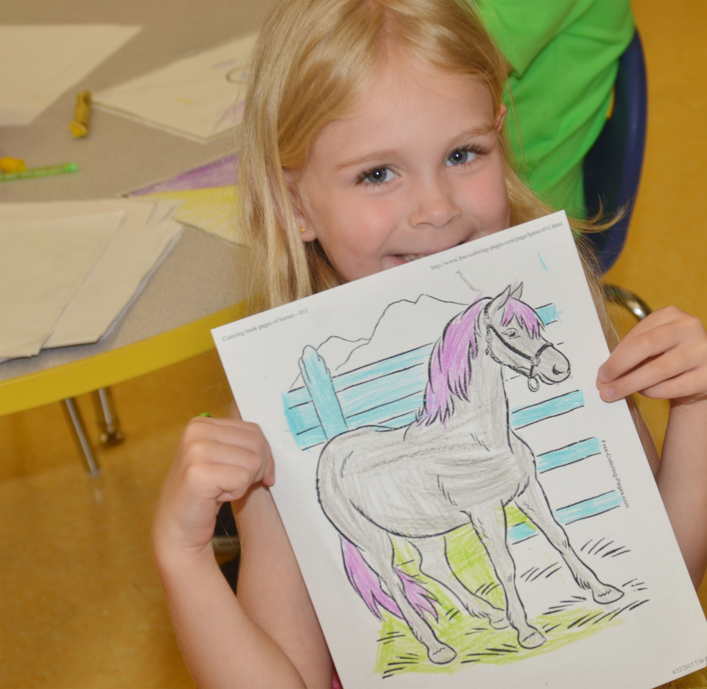 CES preschool student Alinna Bray holds a horse picture she colored.