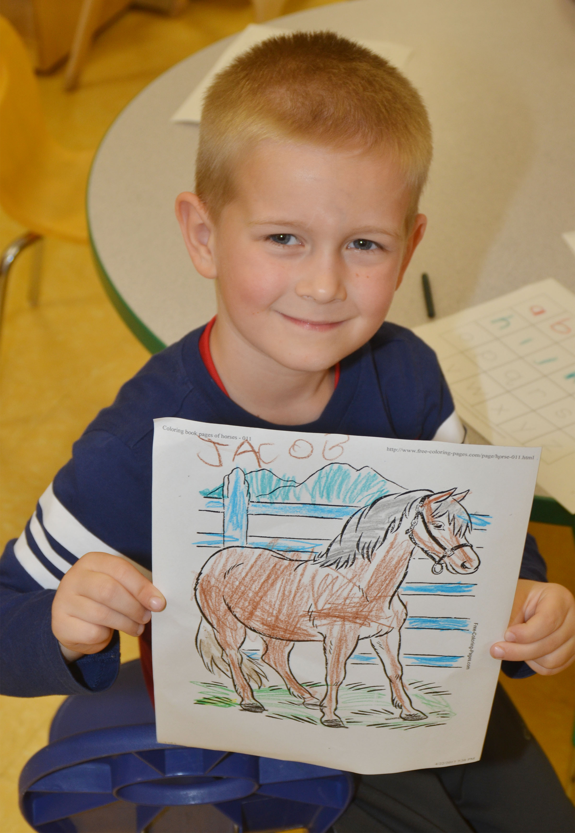 CES preschool student Jacob Parrish holds a horse picture she colored.