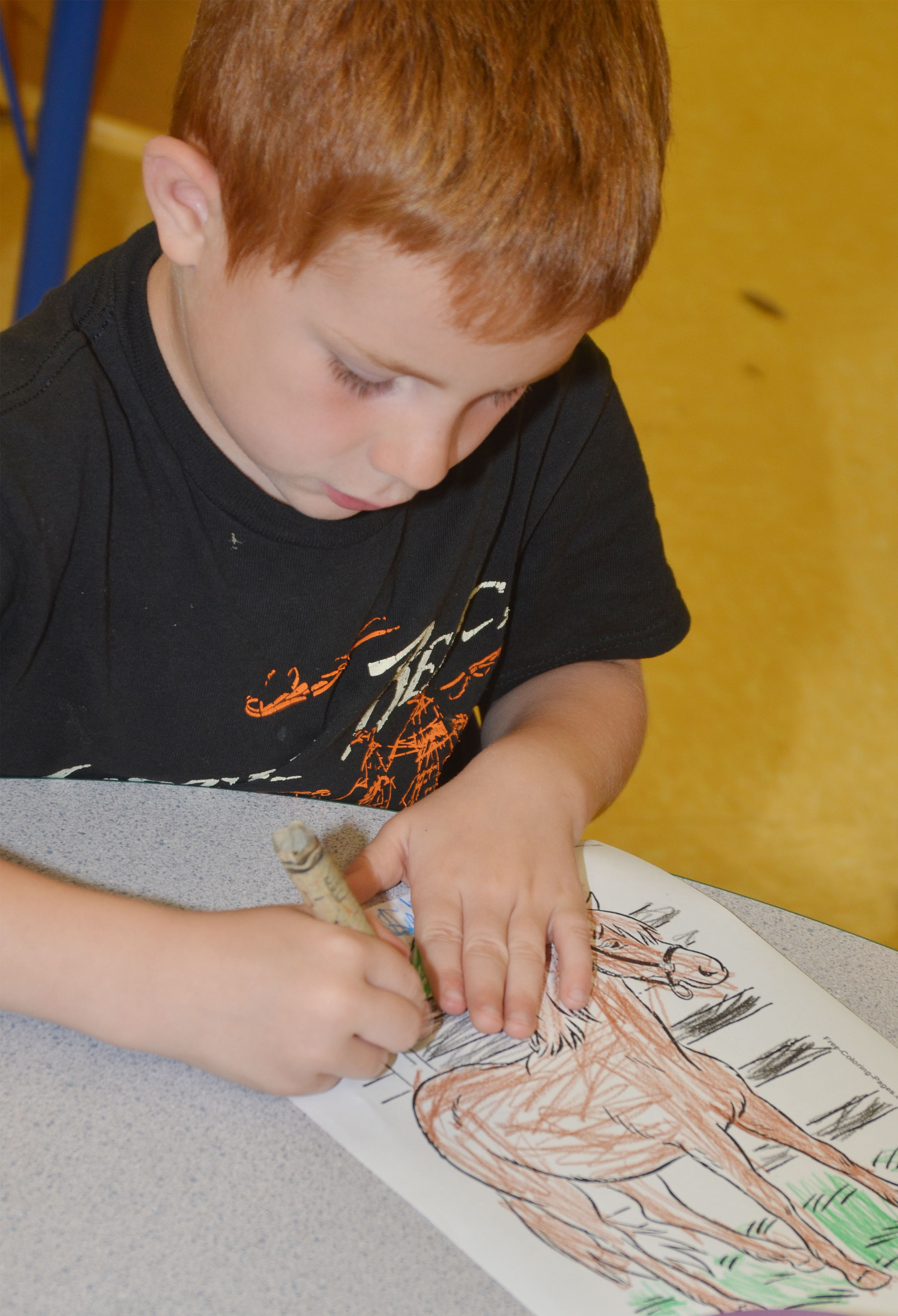 CES preschool student Kennon Dotson colors a horse picture.