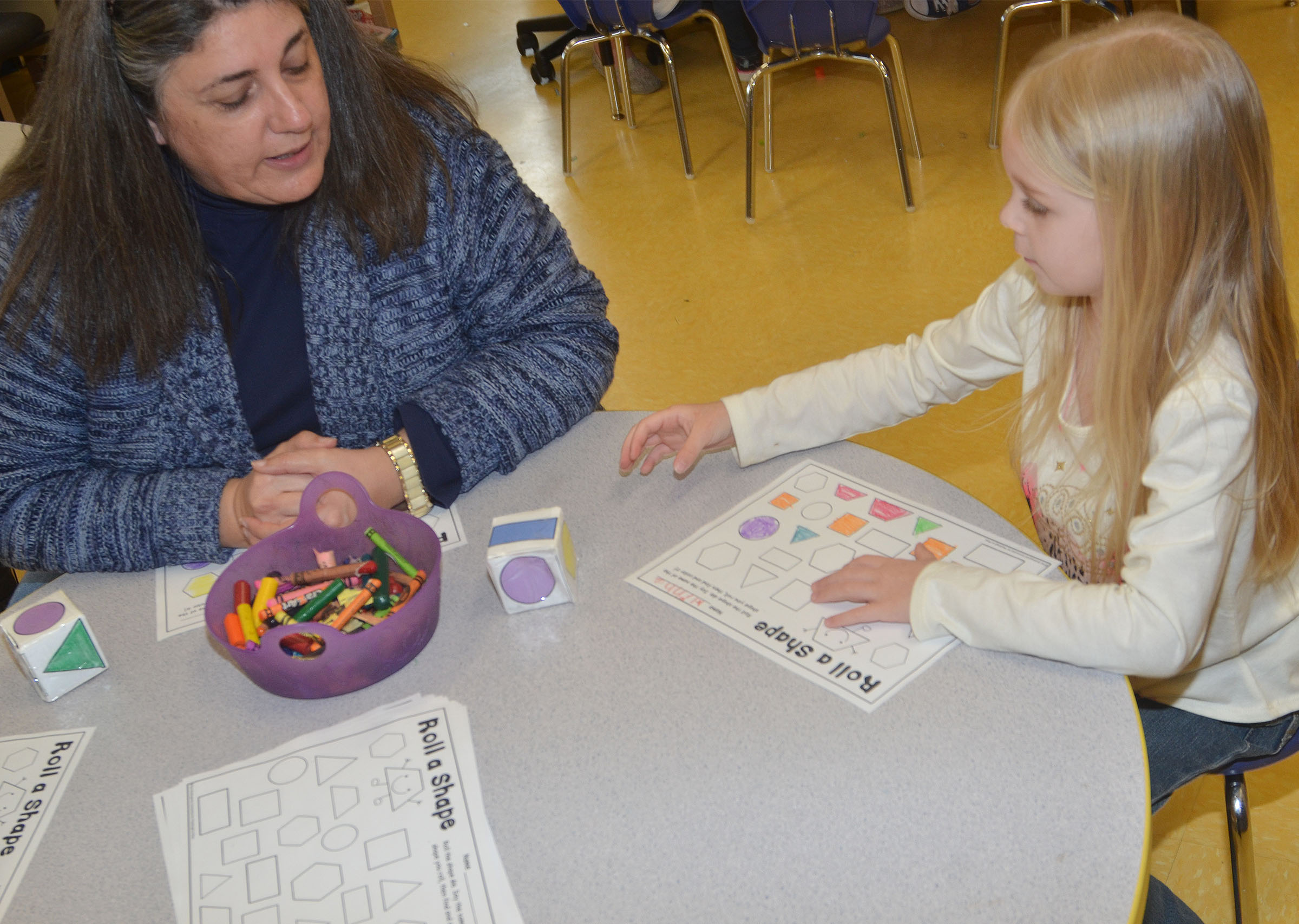 CES preschool teacher Sherry Cowherd plays the Roll a Shape game with Alinna Bray.