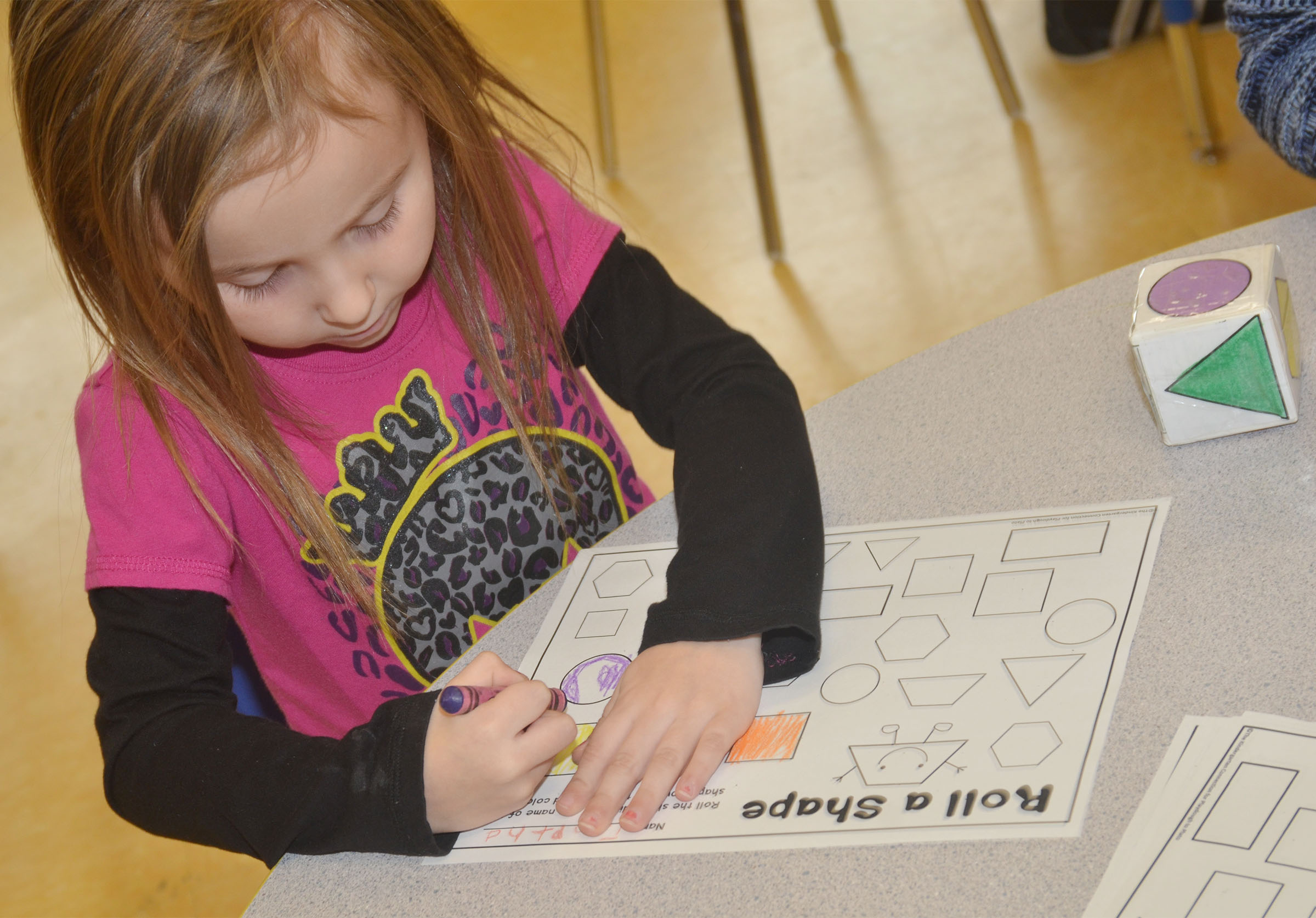 CES preschool student Tabitha Leggett colors a circle purple as she plays the Roll a Shape game.