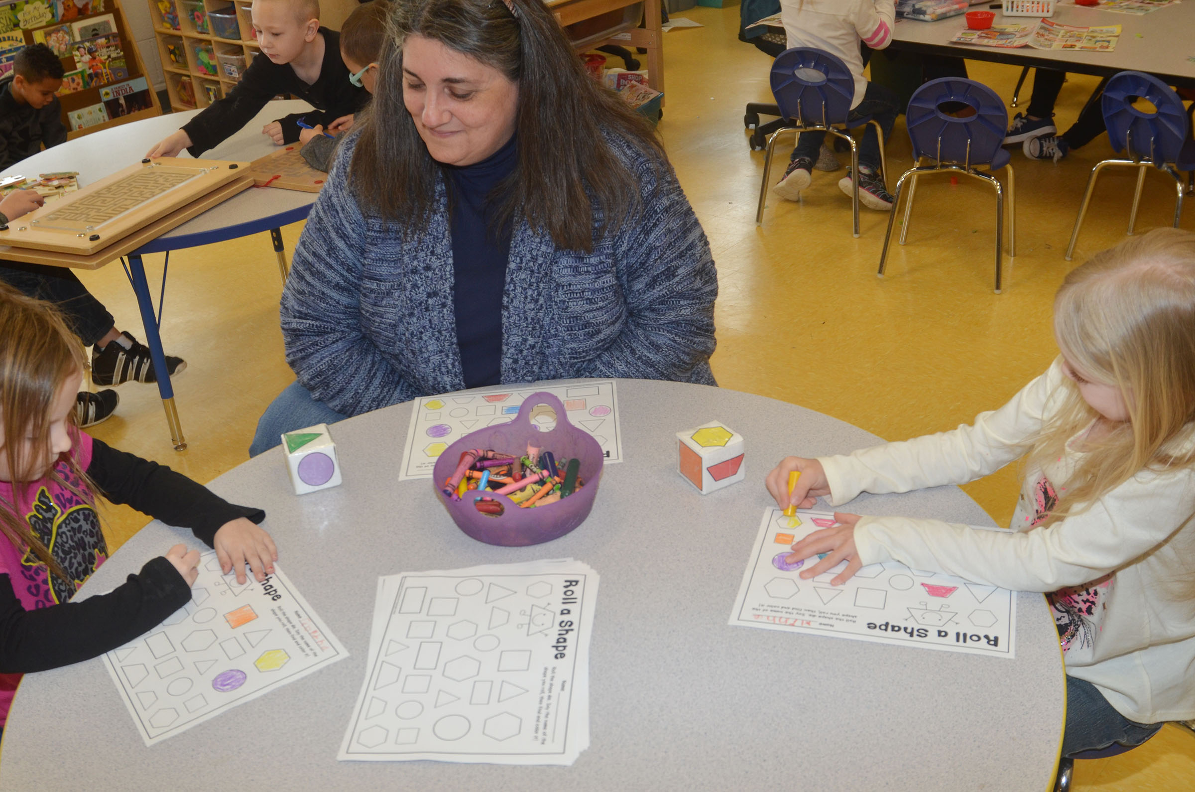 CES preschool teacher Sherry Cowherd plays Roll a Shape with Tabitha Leggett, at left, and Alinna Bray.