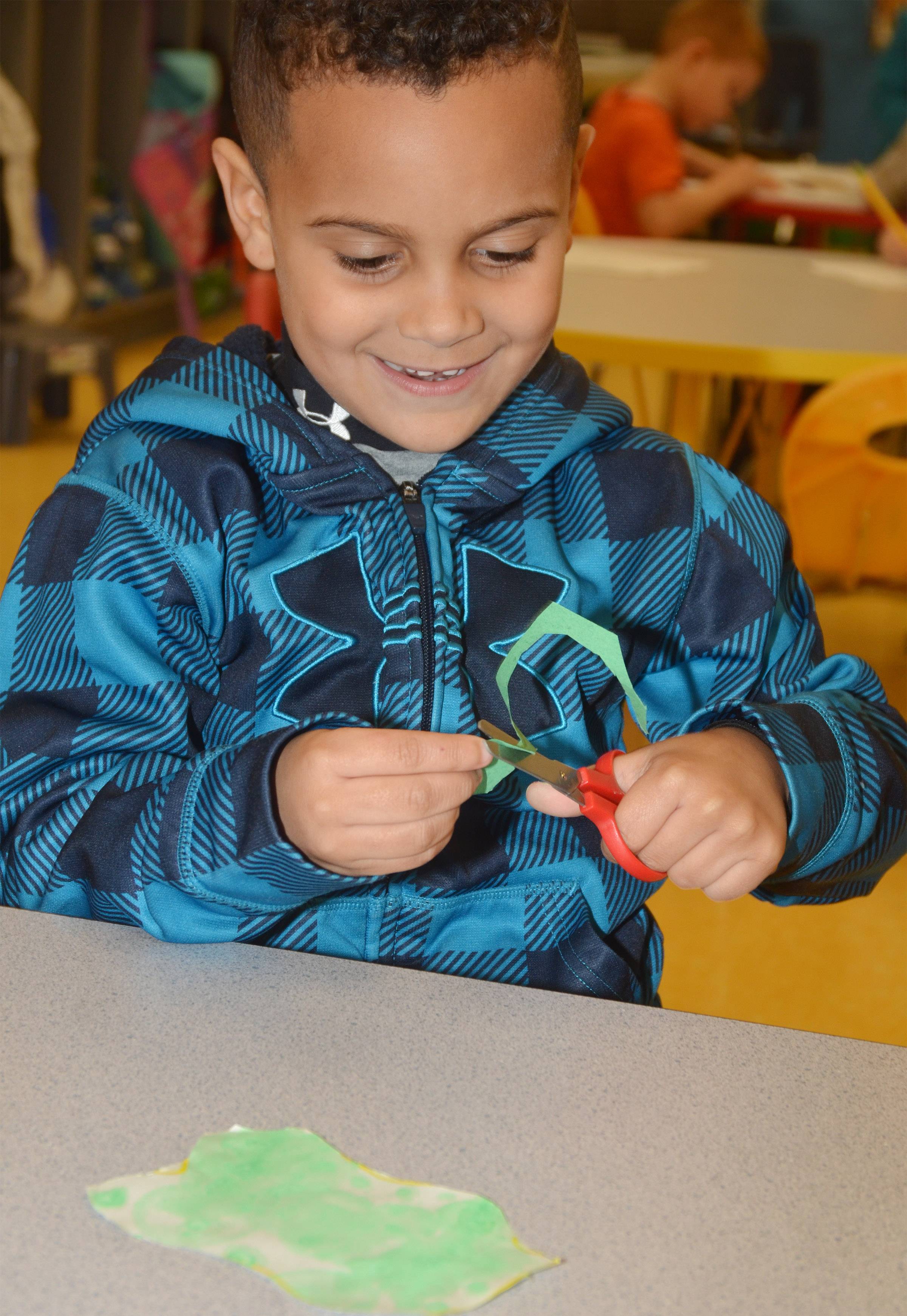 "CES preschool student Kingston Cowherd cuts out his egg for his ""Green Eggs and Ham"" project."
