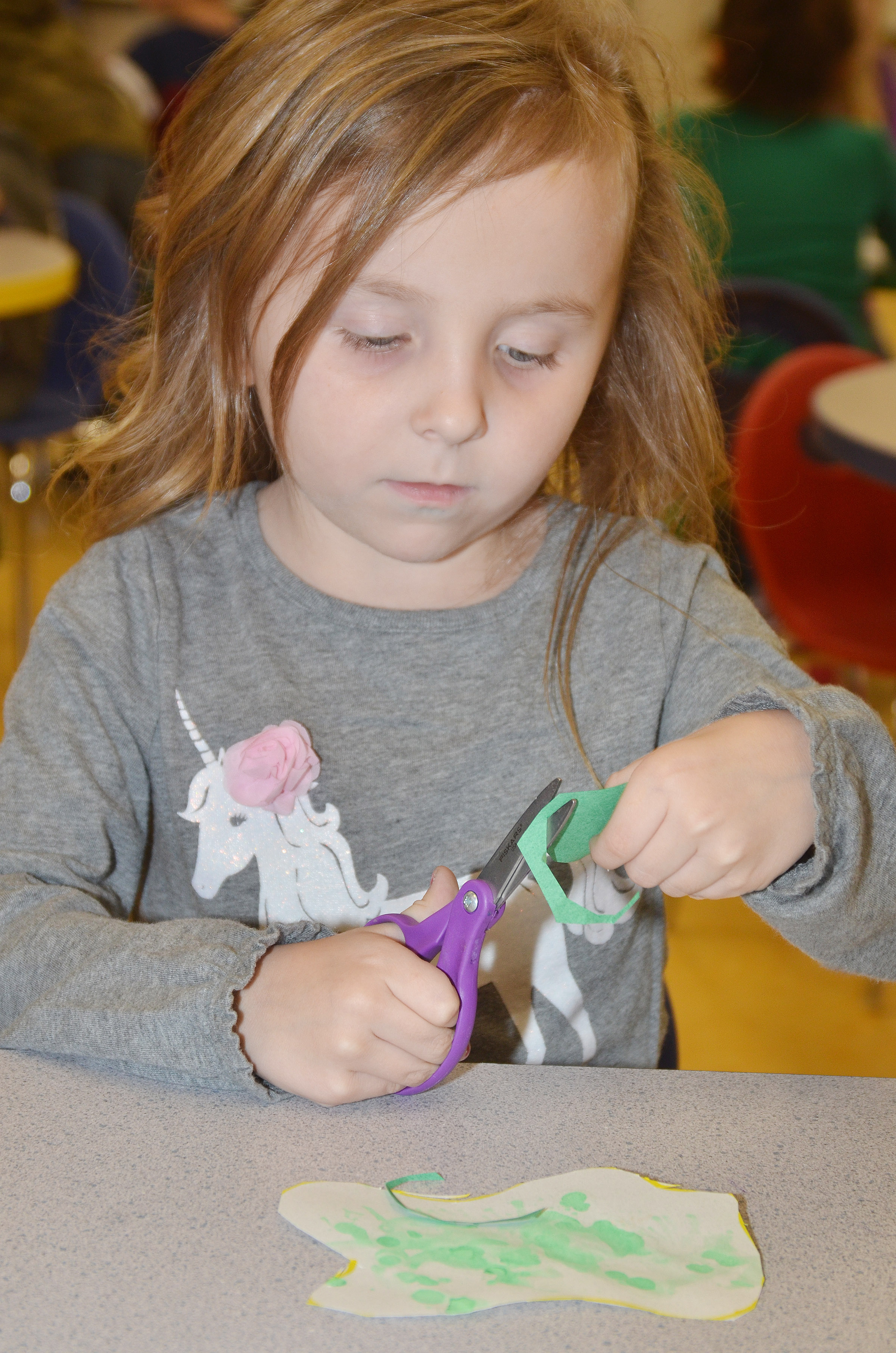 "CES preschool student Tabitha Leggett cuts out her egg for her ""Green Eggs and Ham"" project."
