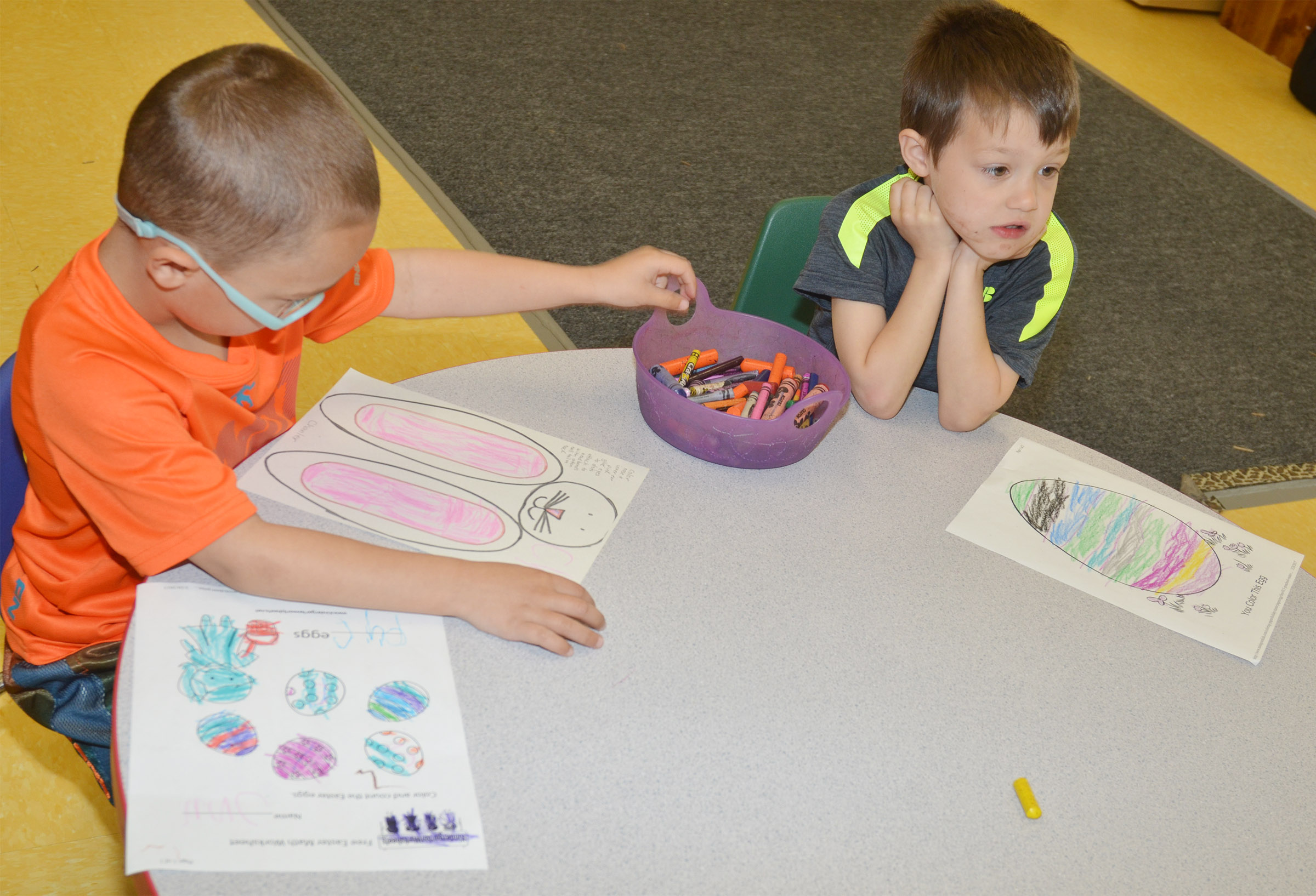 CES preschool students Chanler Mann, at left, and Levi Ritchie color Easter eggs.