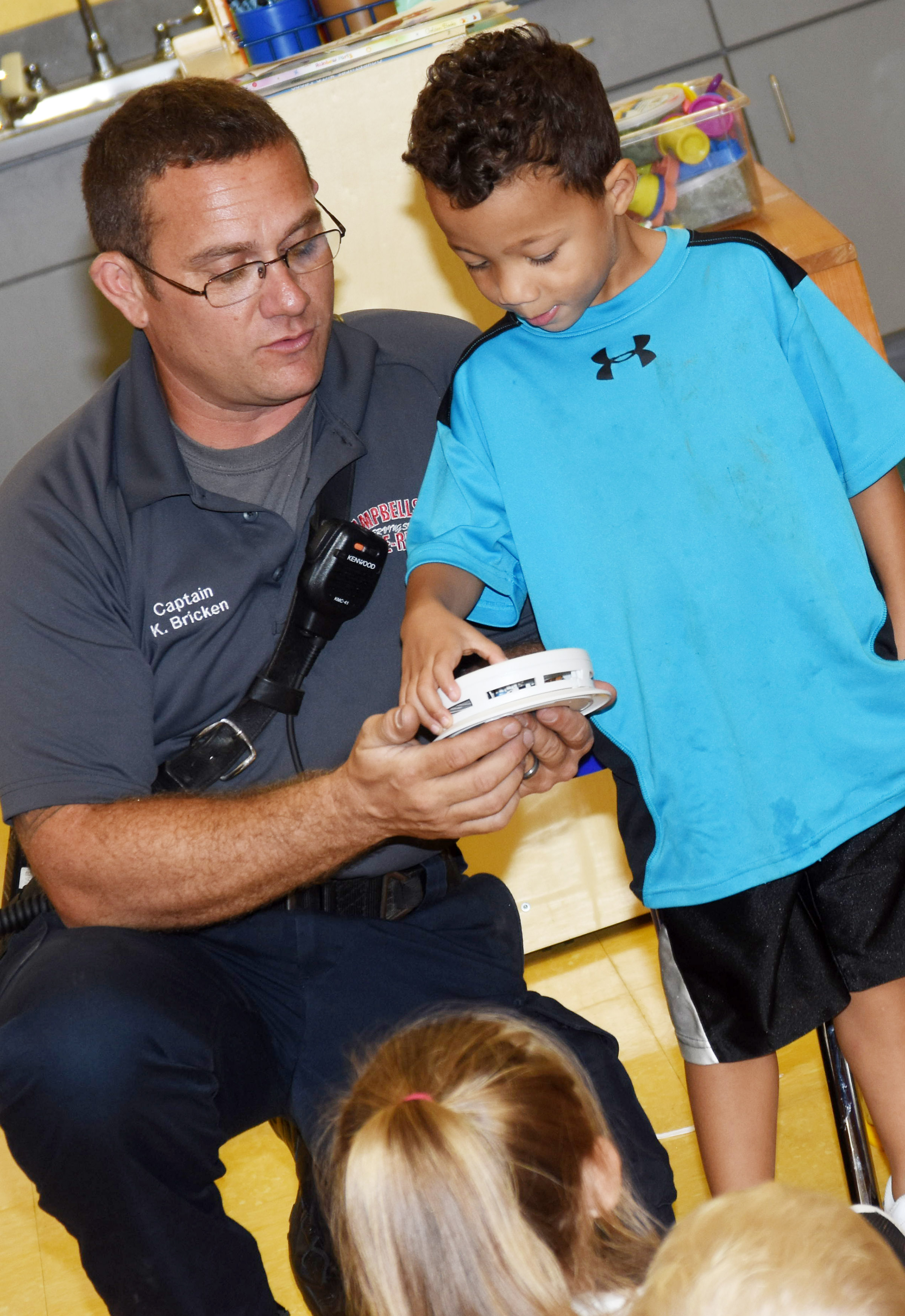 CES preschool student Ace Turner checks the batteries in a smoke detector, with help from Campbellsville Fire & Rescue Captain Keith Bricken.