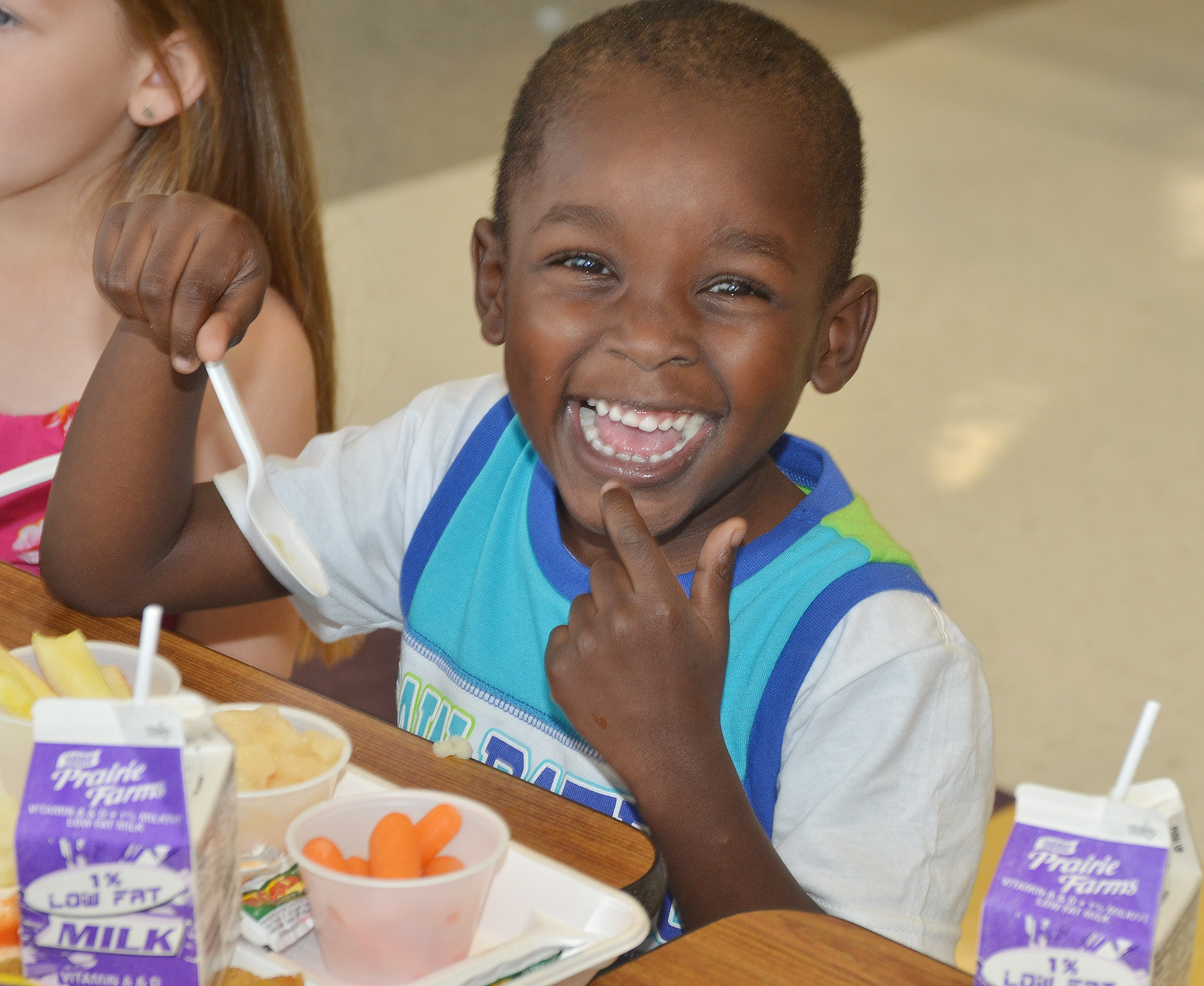 CES preschool student Xavien Smith smiles as he eats lunch.