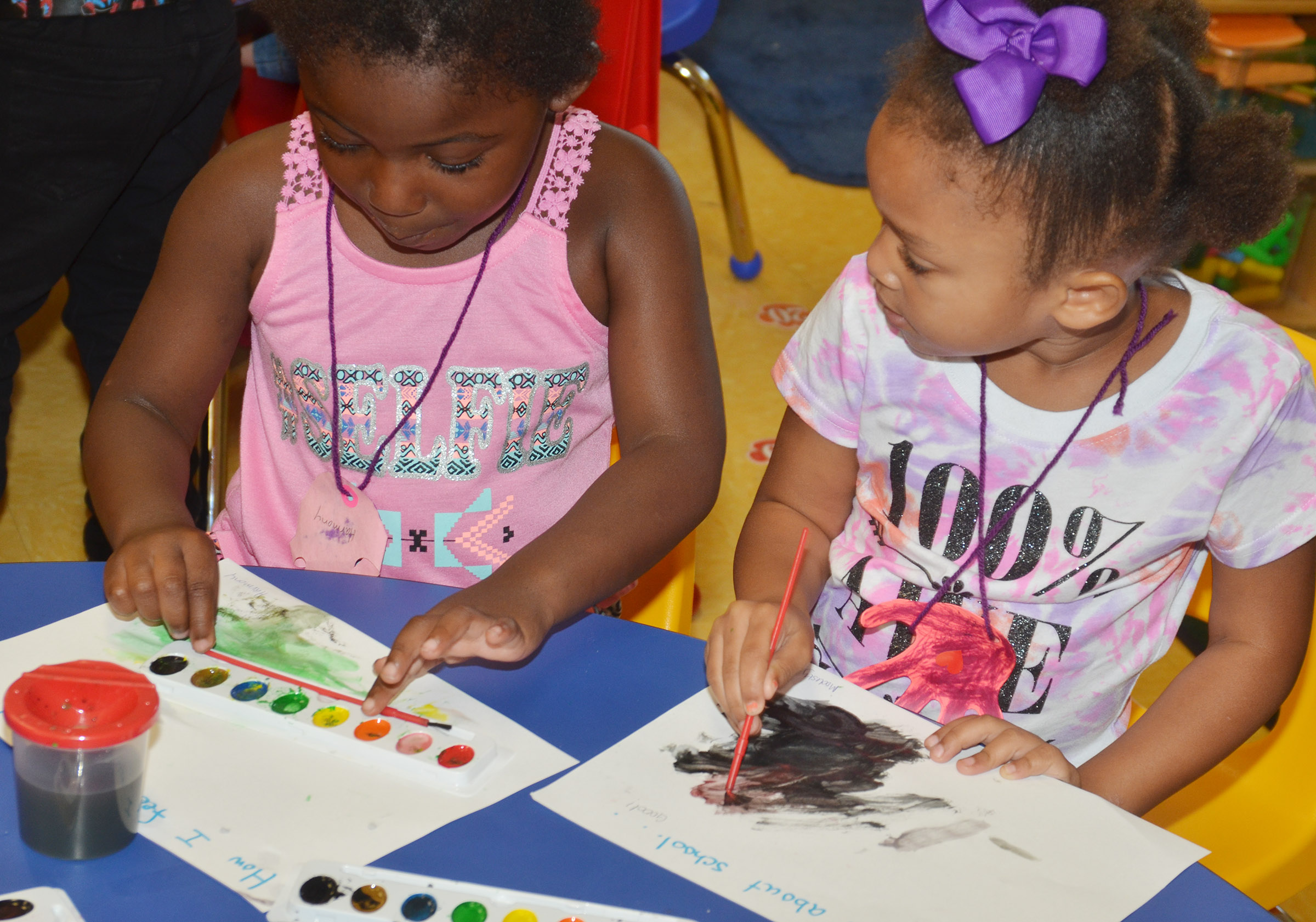 CES preschool students Harmony Brown, at left, and Modesty Taylor talk as they paint how they felt about coming to preschool.