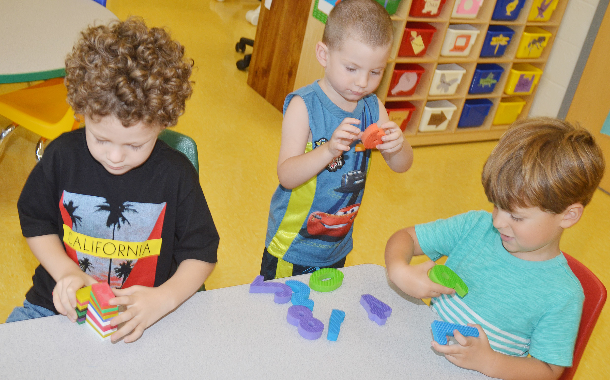 From left, CES preschool students Zyron Young, Chase Arnett and David Smith play together.