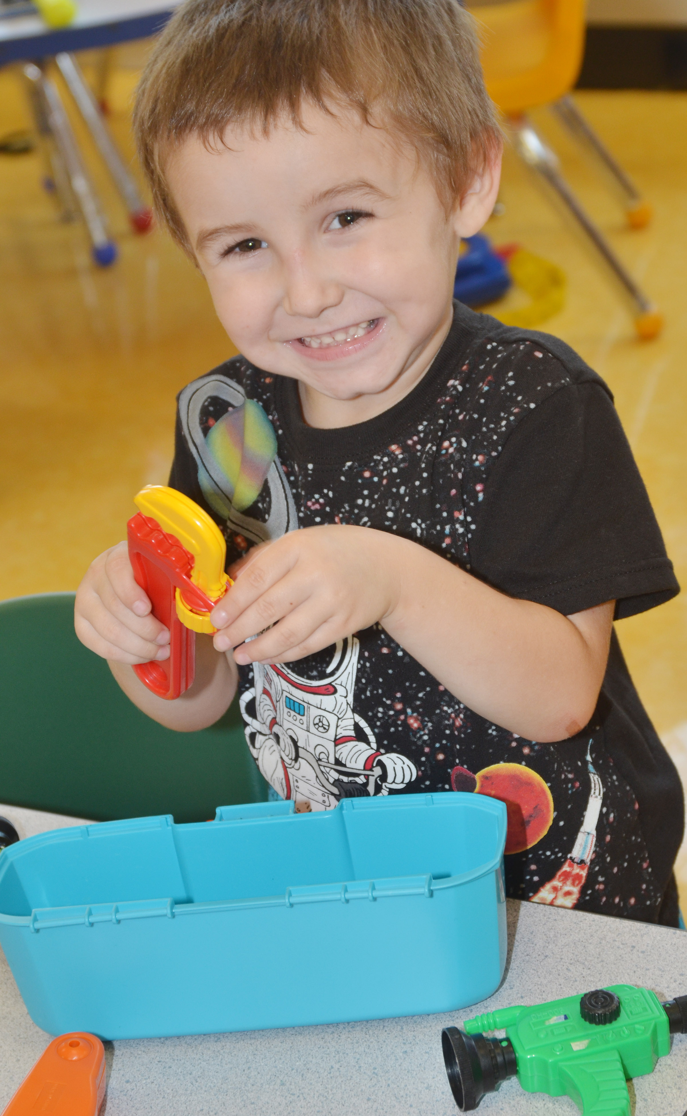 CES preschool student Noelan McMahan smiles as he plays with his tools.