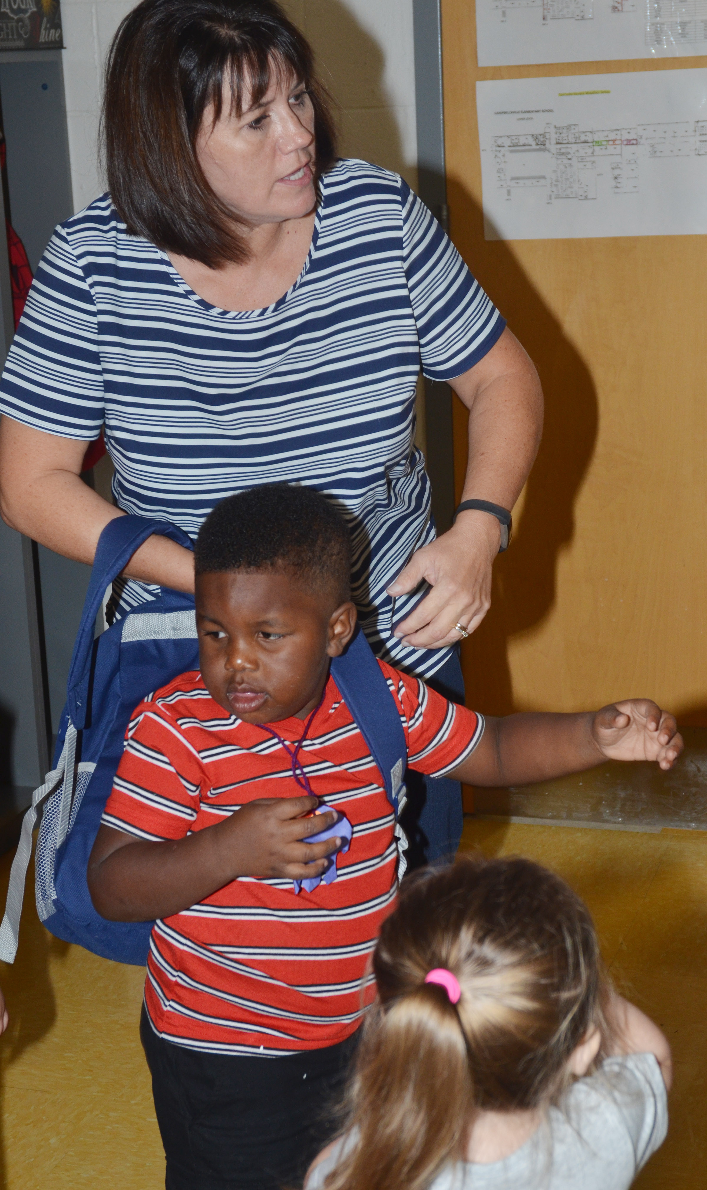 CES preschool teacher Denise Spencer helps student Kareem Smith put on his backpack as he prepares to go home after the first day of school.