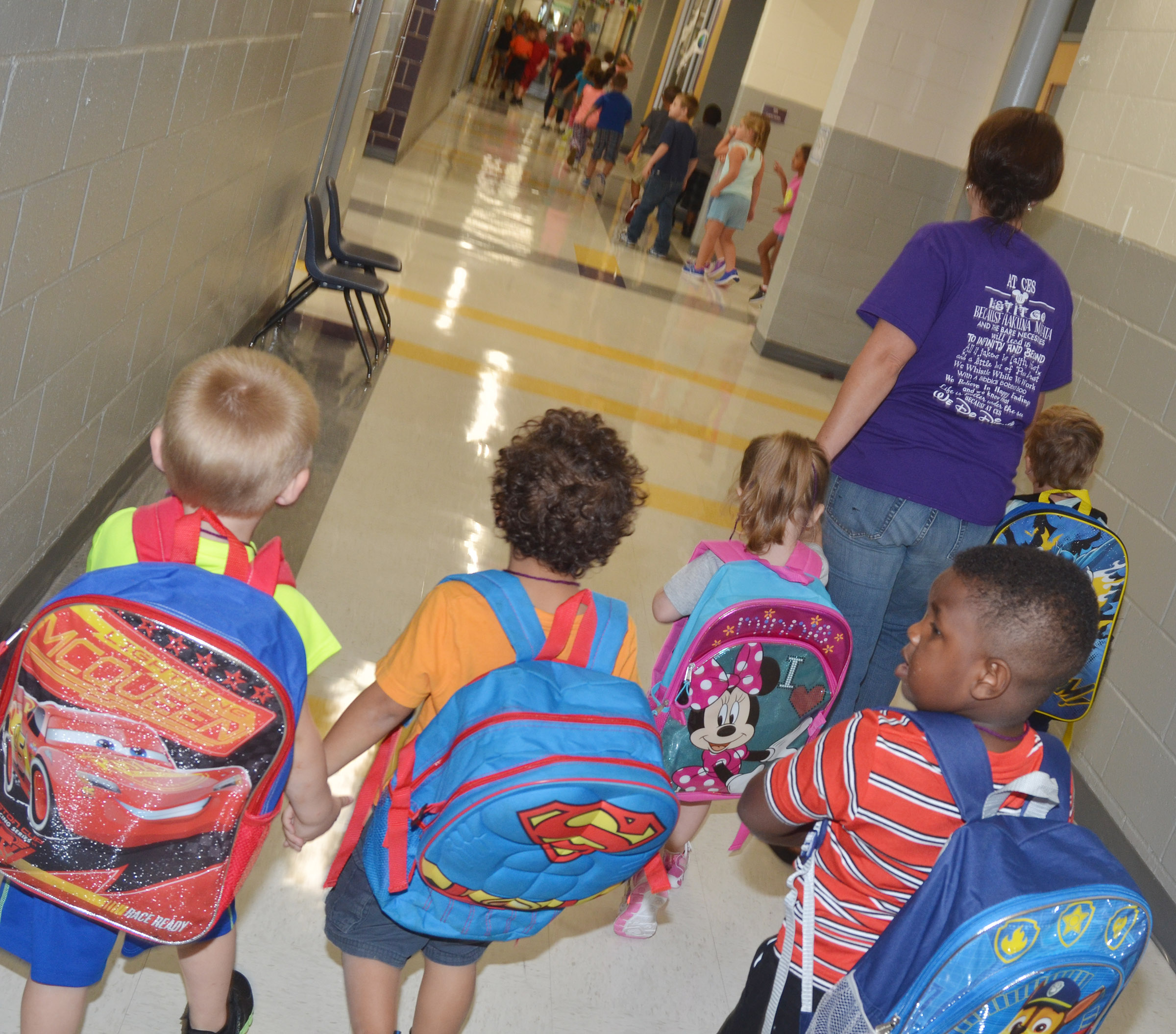 CES preschool assistant Beth Sandidge leads preschool students as they walk down the hallway to board the school bus.