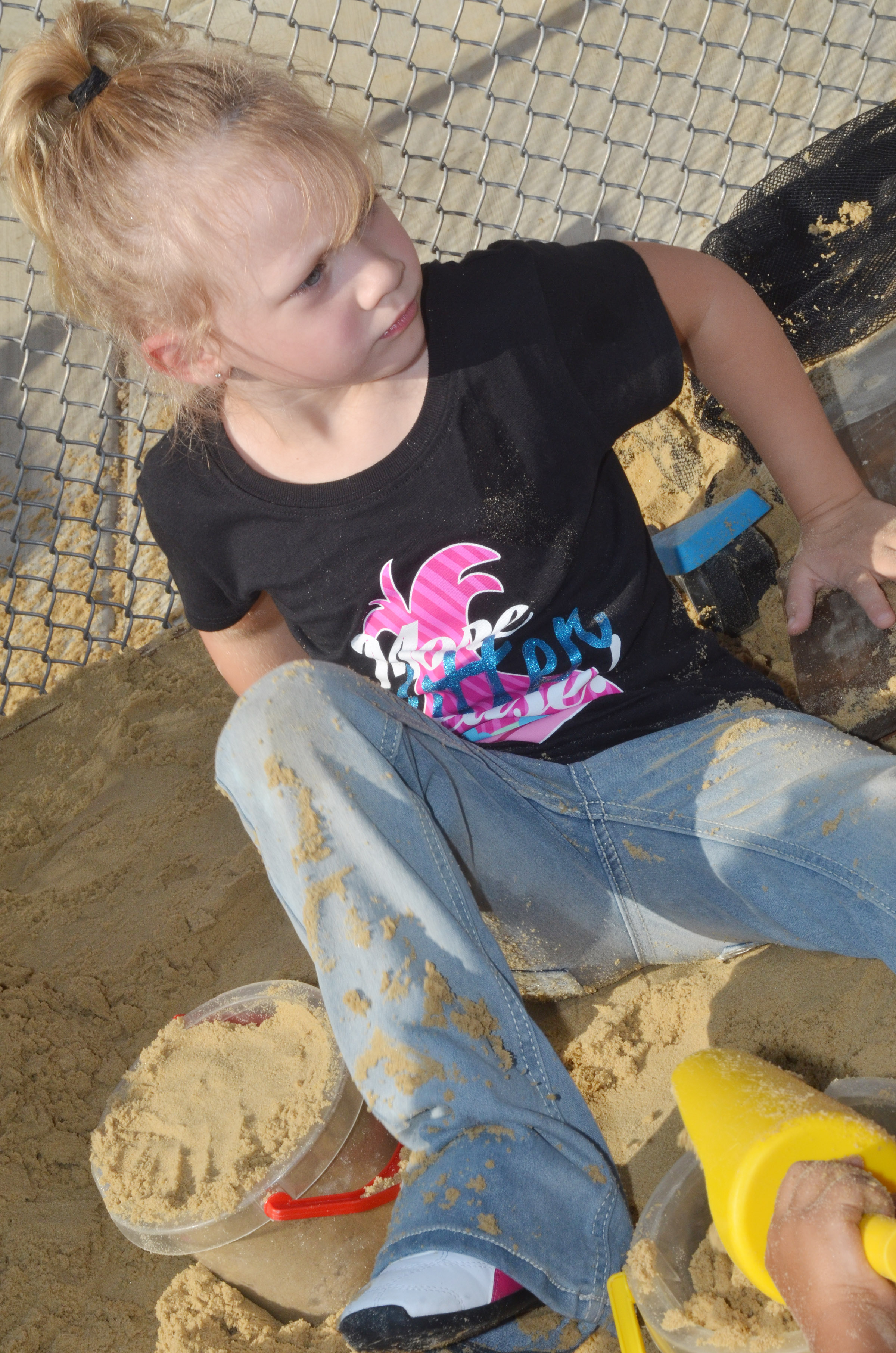 CES preschool student Aubree Hall plays in the sandbox.