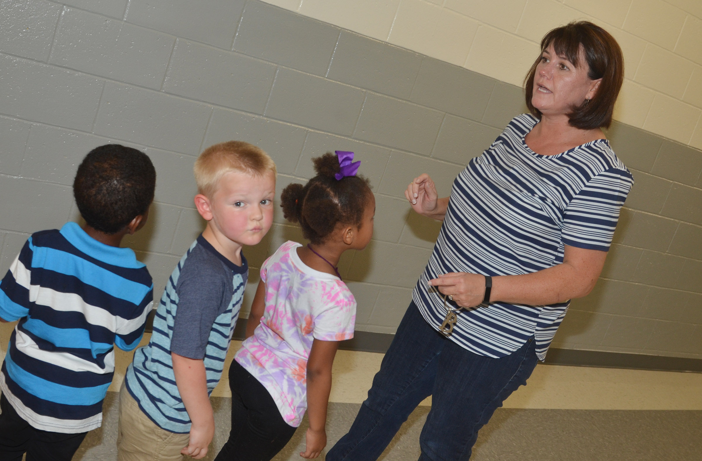 CES preschool teacher Denise Spencer shows her students, from left, Rakim Dunn, Hoyt Davis and Modesty Taylor how to line up in the hallway.