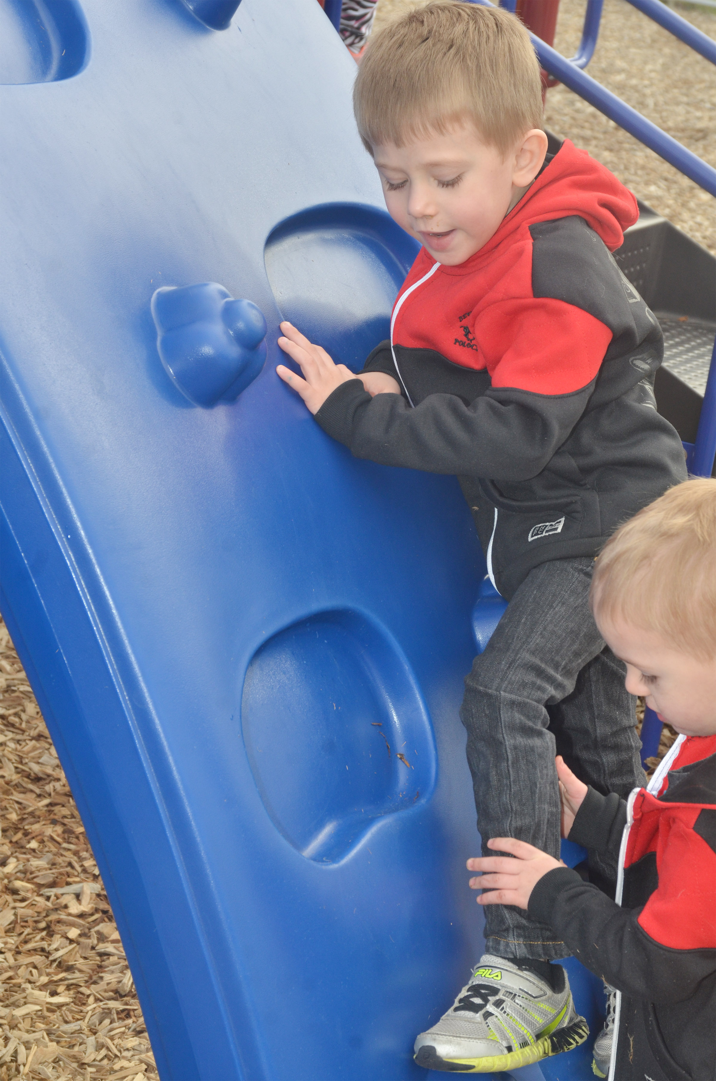 CES preschool students Elijah Russell, at top, and his brother, Chase, climb as they and their classmates enjoy some playground time.