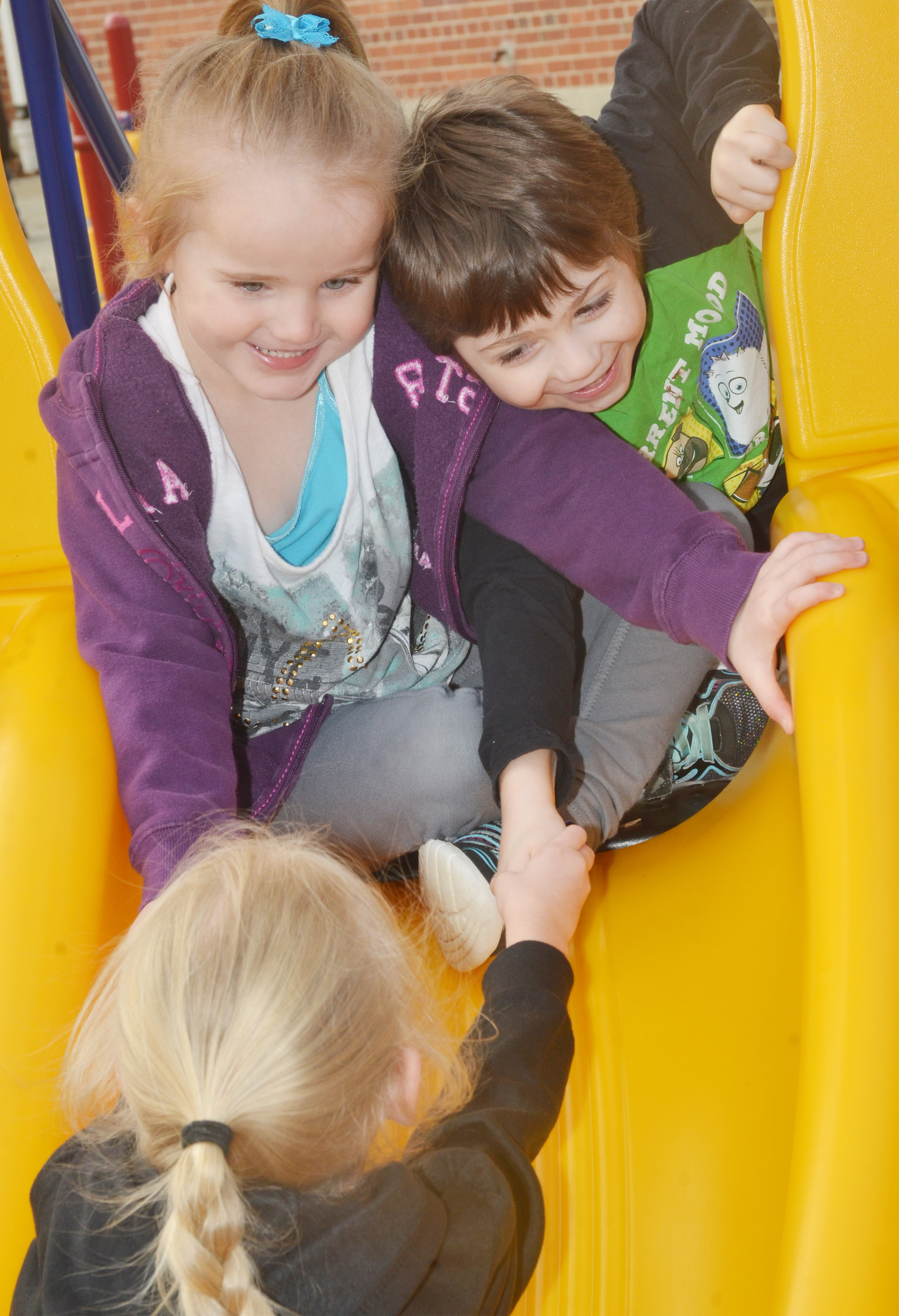 CES preschool students Trinity Dye, at left, and Josiah Dean laugh as they slide down the slide – with some help from Alinna Bray – as they and their classmates enjoy some playground time.