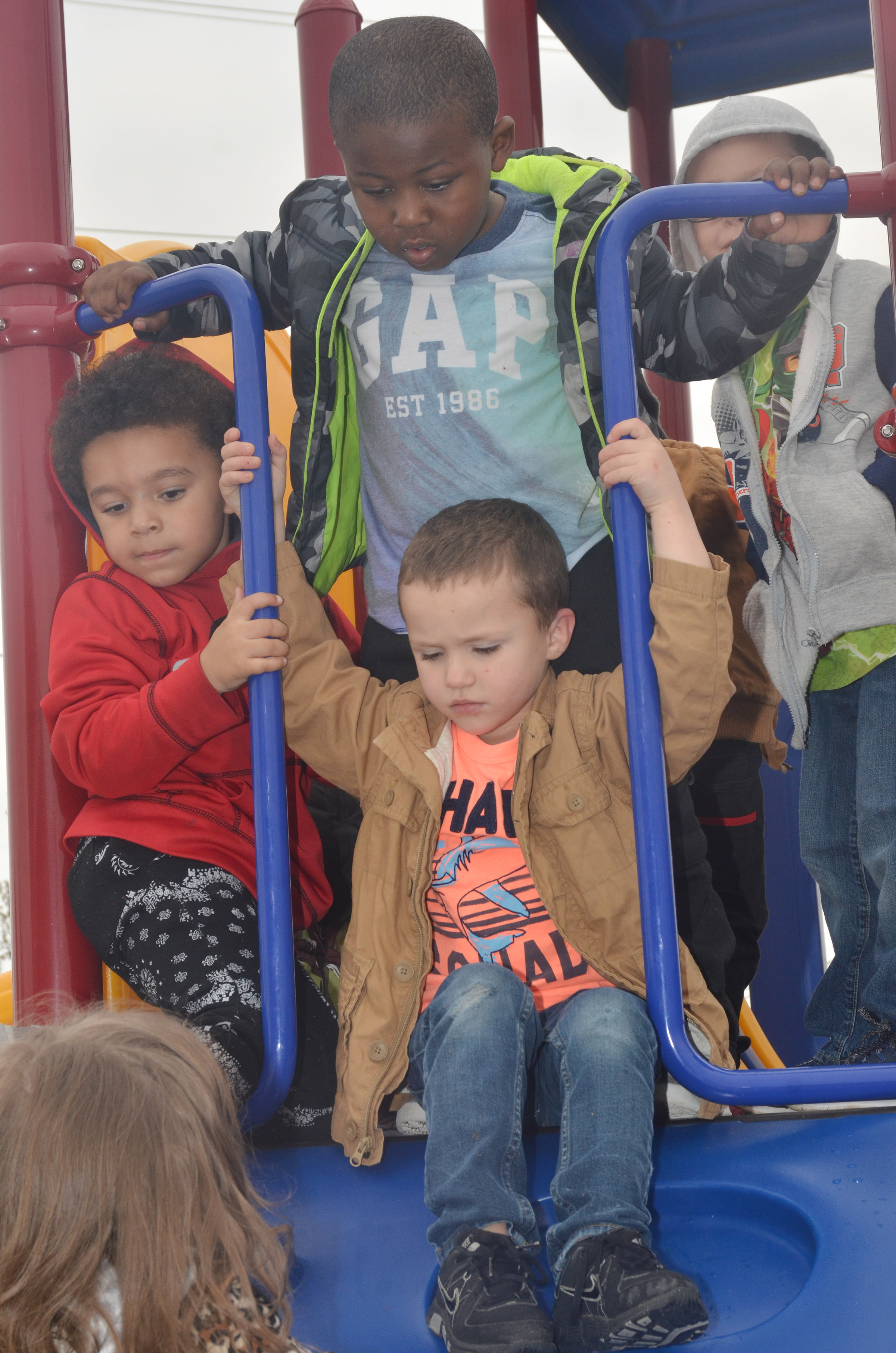 CES preschool student Triton Bradshaw climbs as his classmates Tyrek Moore, at left, and LaTayvion Brown wait their turn, as they and their classmates enjoy some playground time.