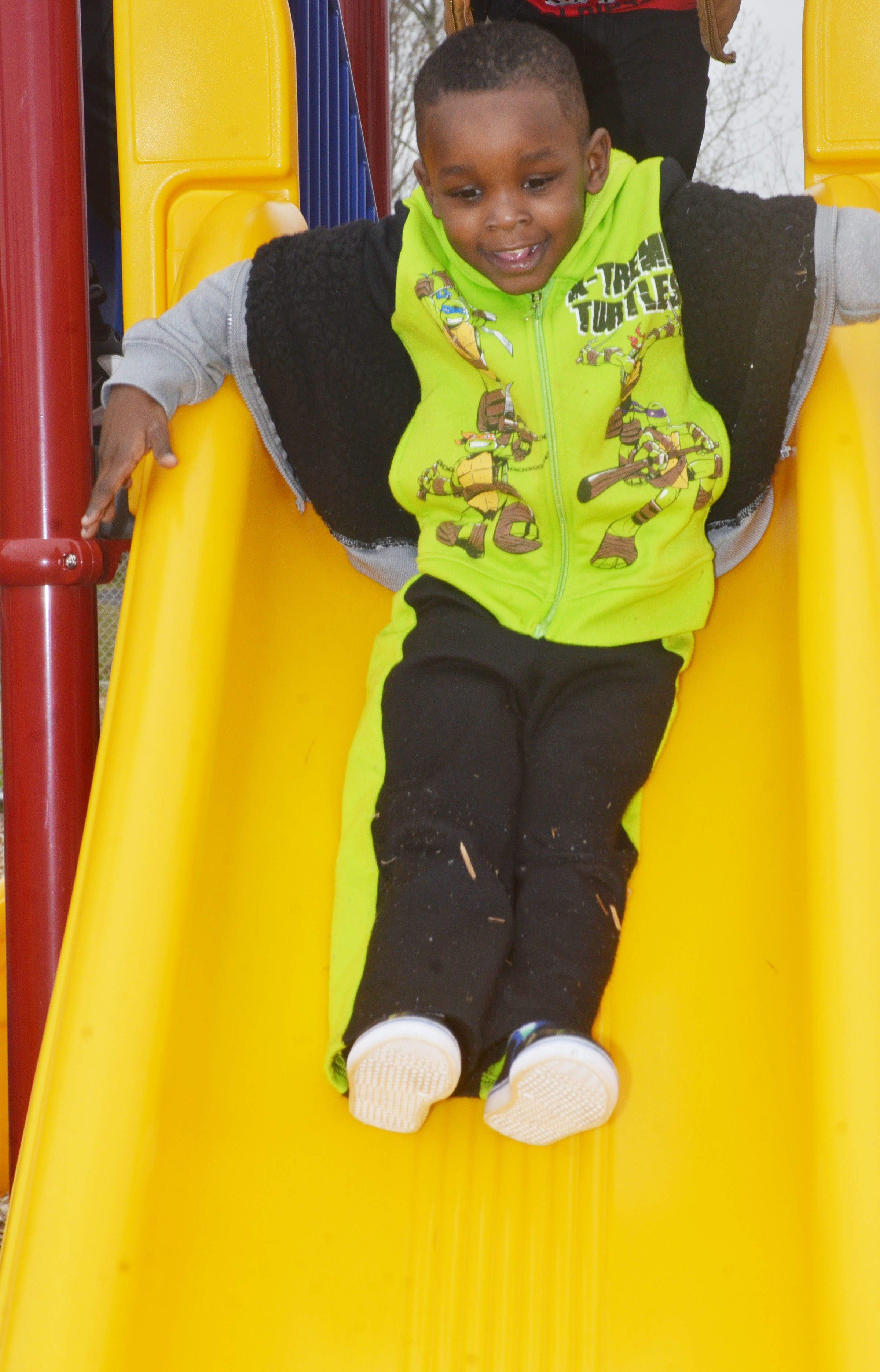 CES preschool student Xavien Smith slides down the slide as he and his classmates enjoy some playground time.
