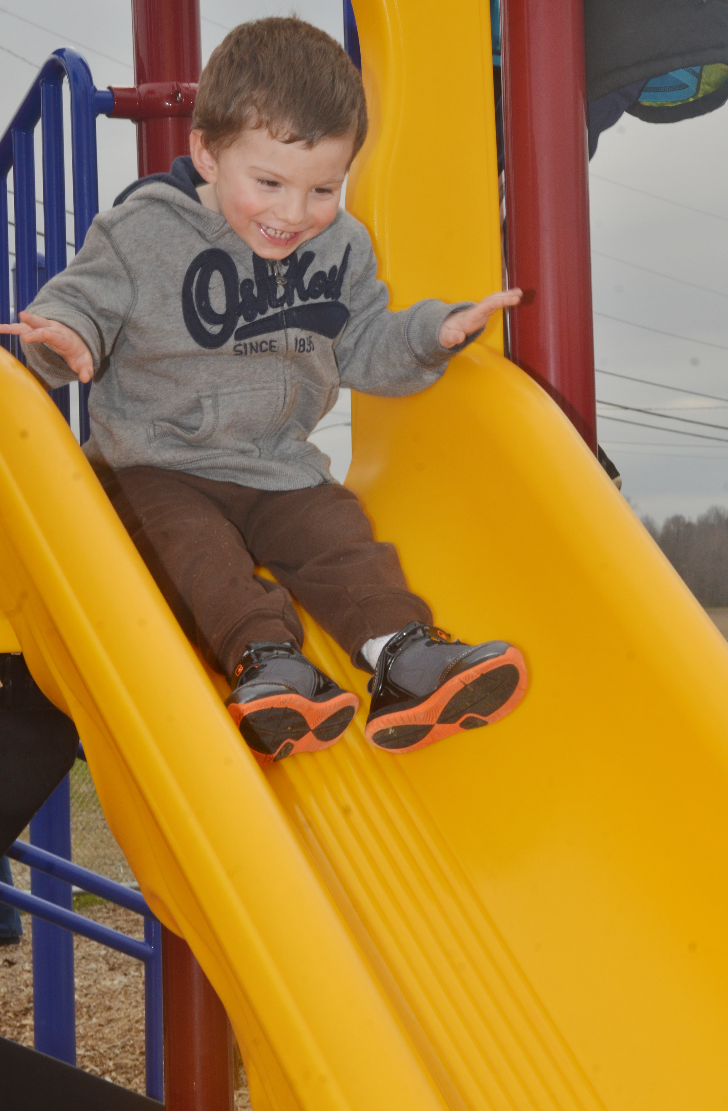 CES preschool student Chase Arnett slides down the slide as he and his classmates enjoy some playground time.