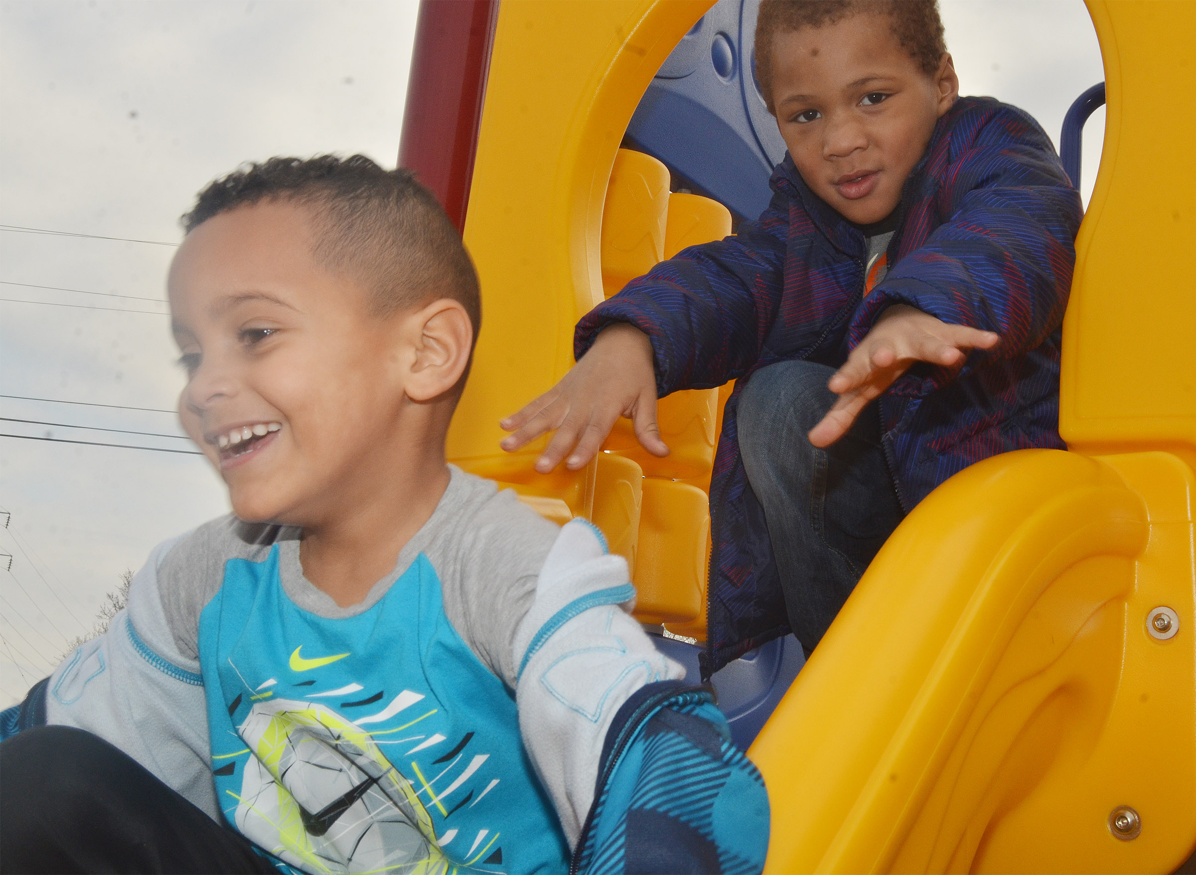CES preschool student Kingstown Cowherd slides down the slide as Jamerius Miller waits his turn, as they and their classmates enjoy some playground time.