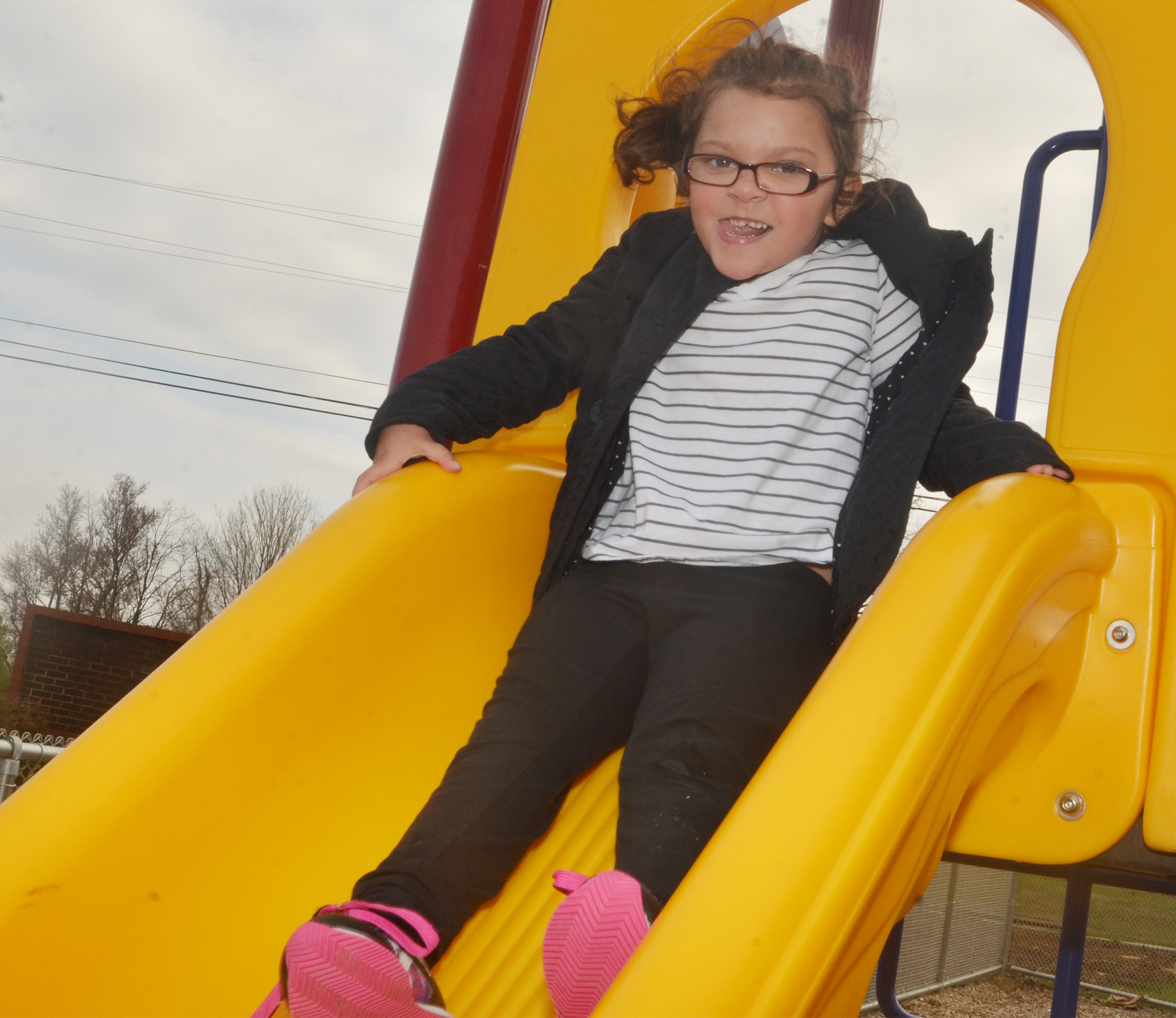 CES preschool student Addisyn Taylor slides down the slide as she and her classmates enjoy some playground time.