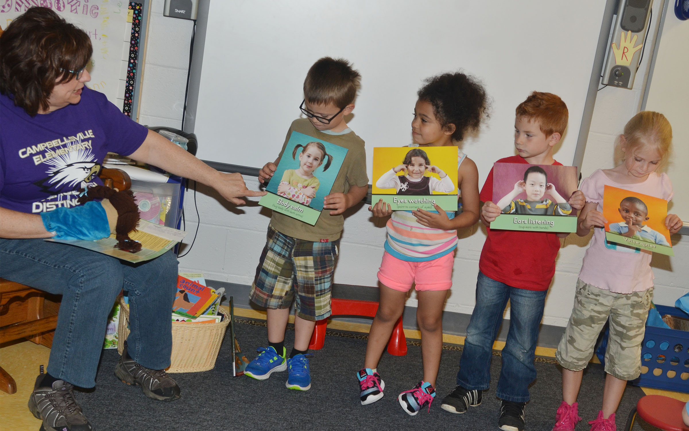 Susan Kennon, a Campbellsville Family Resource and Youth Services Center liaison at CES, talks to CES preschool students about how they should manage their behavior in kindergarten. From left are Reece Williams, Rylee Karr, Kennon Dotson and Alinna Bray.