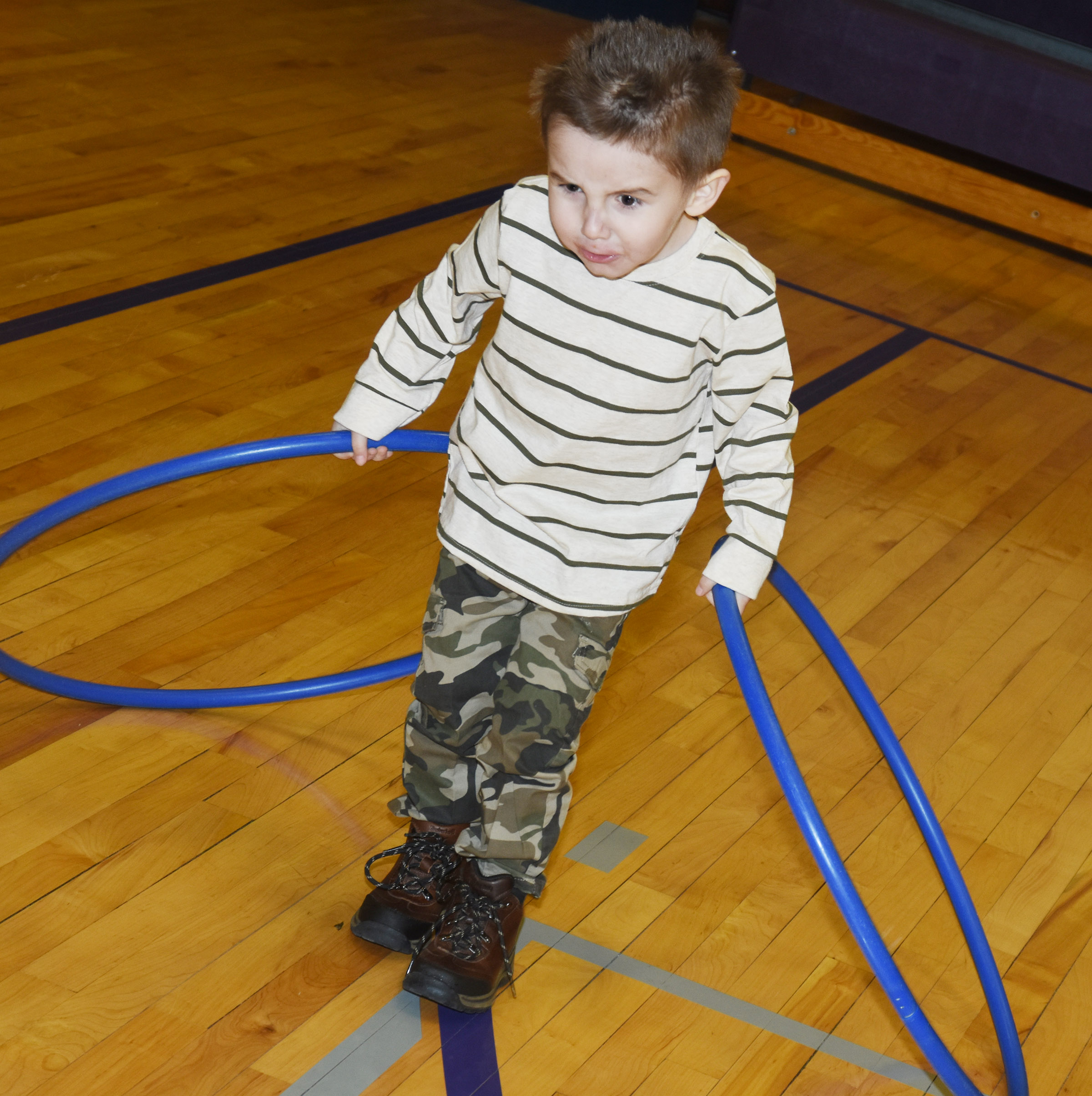 CES preschool student Noelan McMahan runs in the gym with his hula hoops.