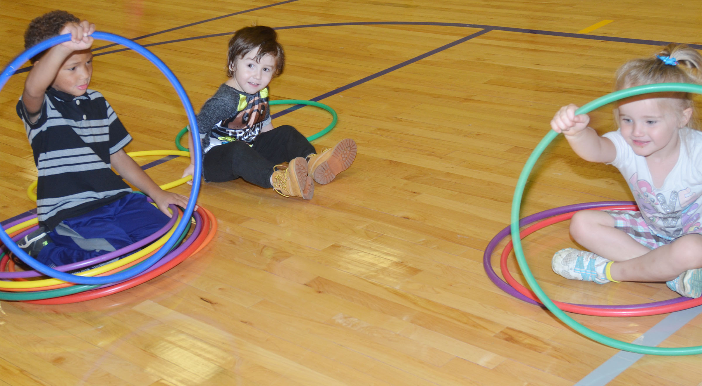 From left, CES preschool students Jamerius Miller, Noelan McMahan and Trinity Dye play with hula hoops.