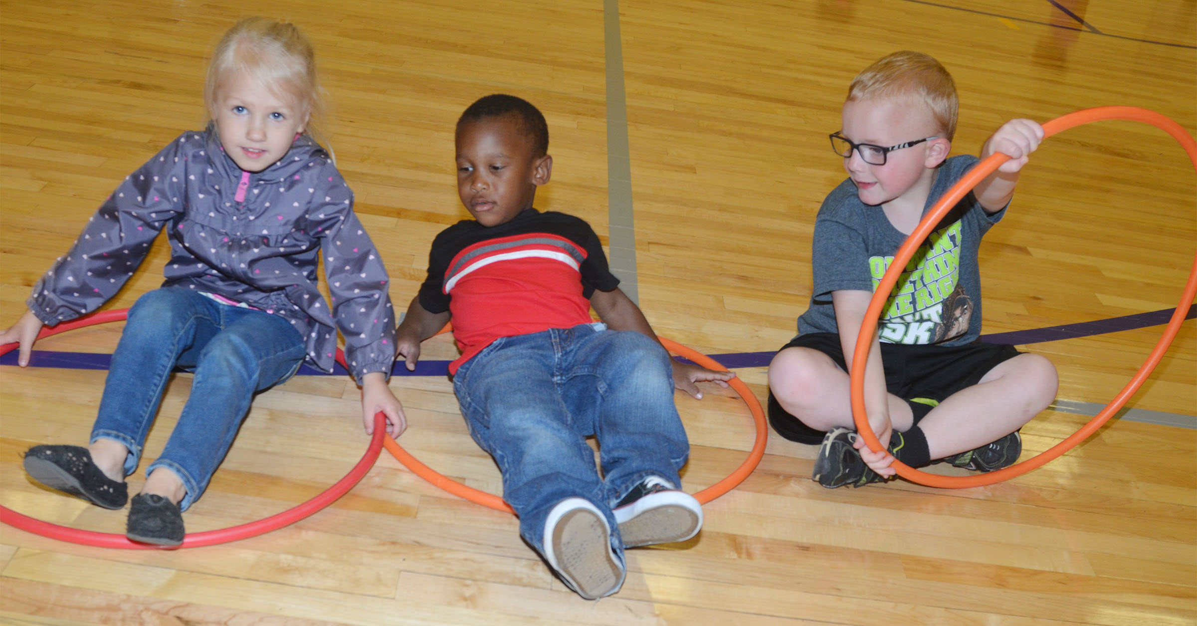 From left, CES preschool students Trinity Lewis, Mason Conner and Anthony McClure play with hula hoops.