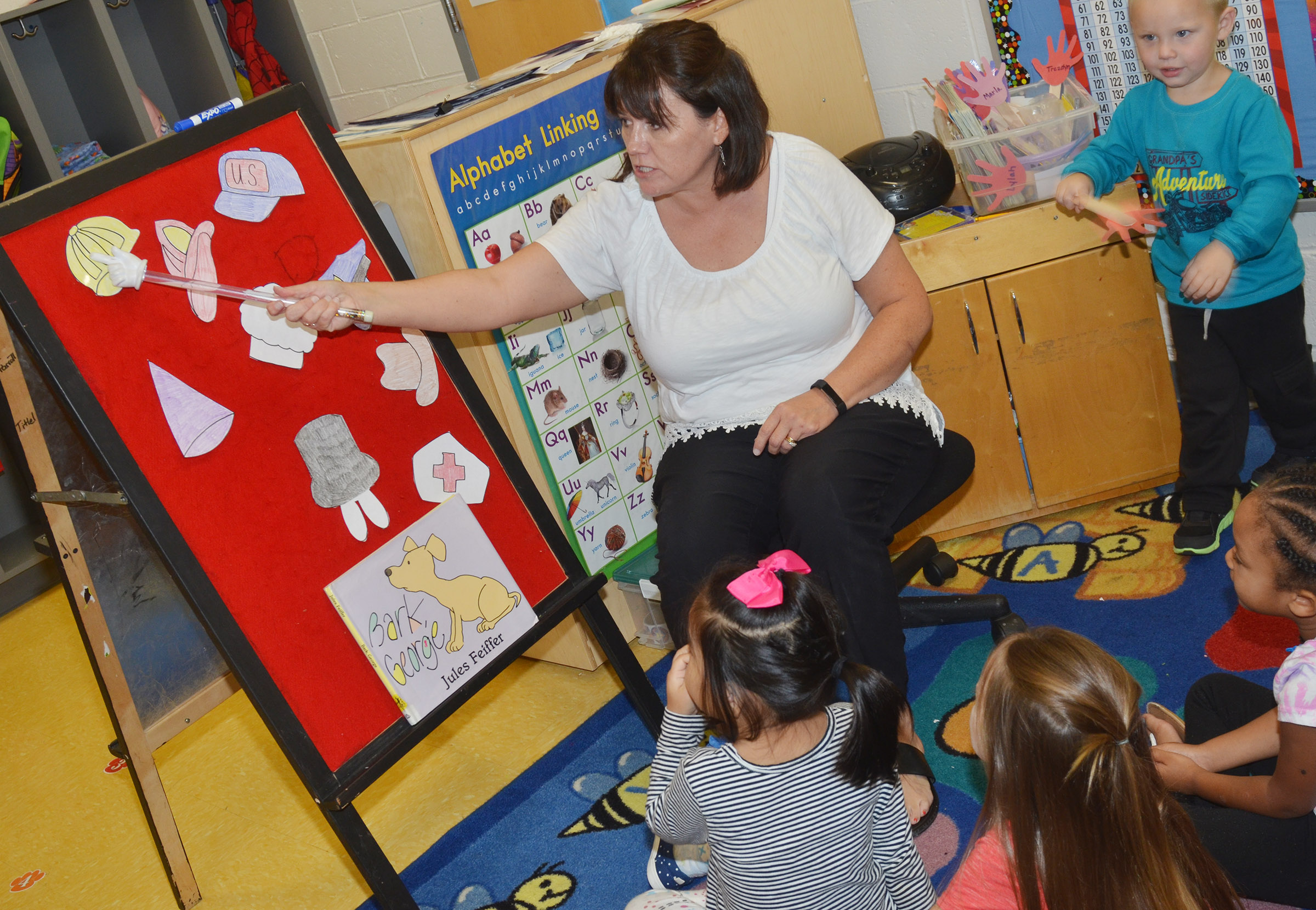 CES preschool teacher Denise Spencer asks her students under which hat they believe the mouse has chosen to hide.