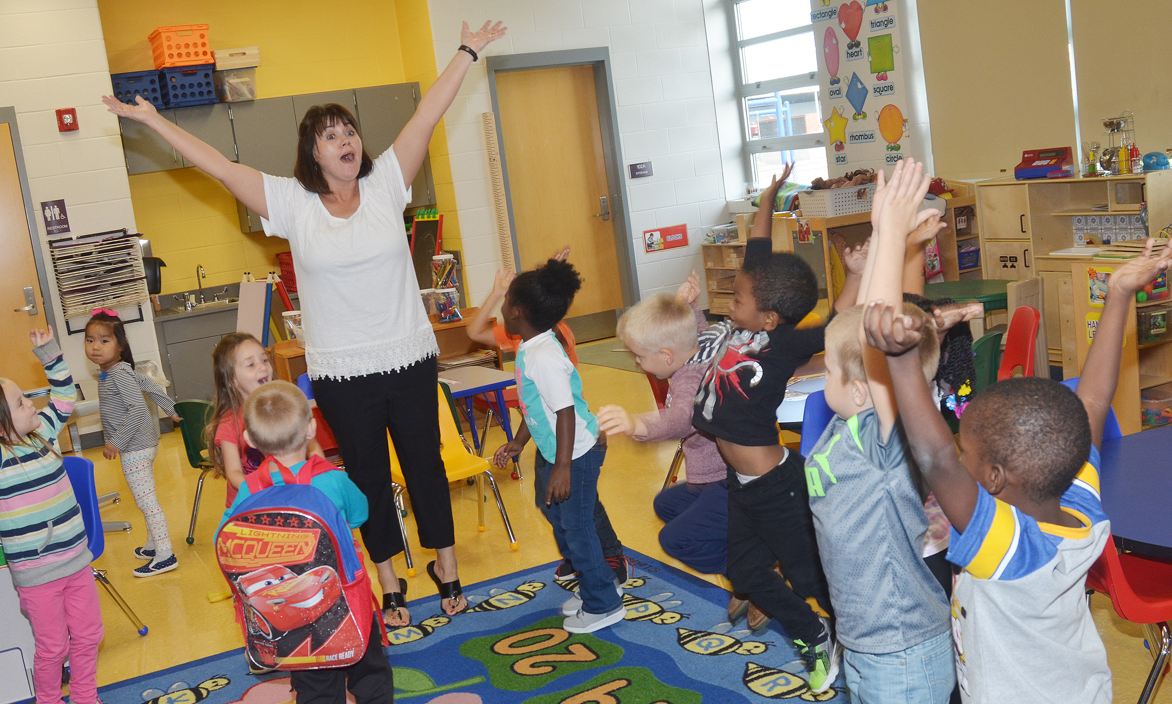 CES preschool teacher Denise Spencer dances with her students.