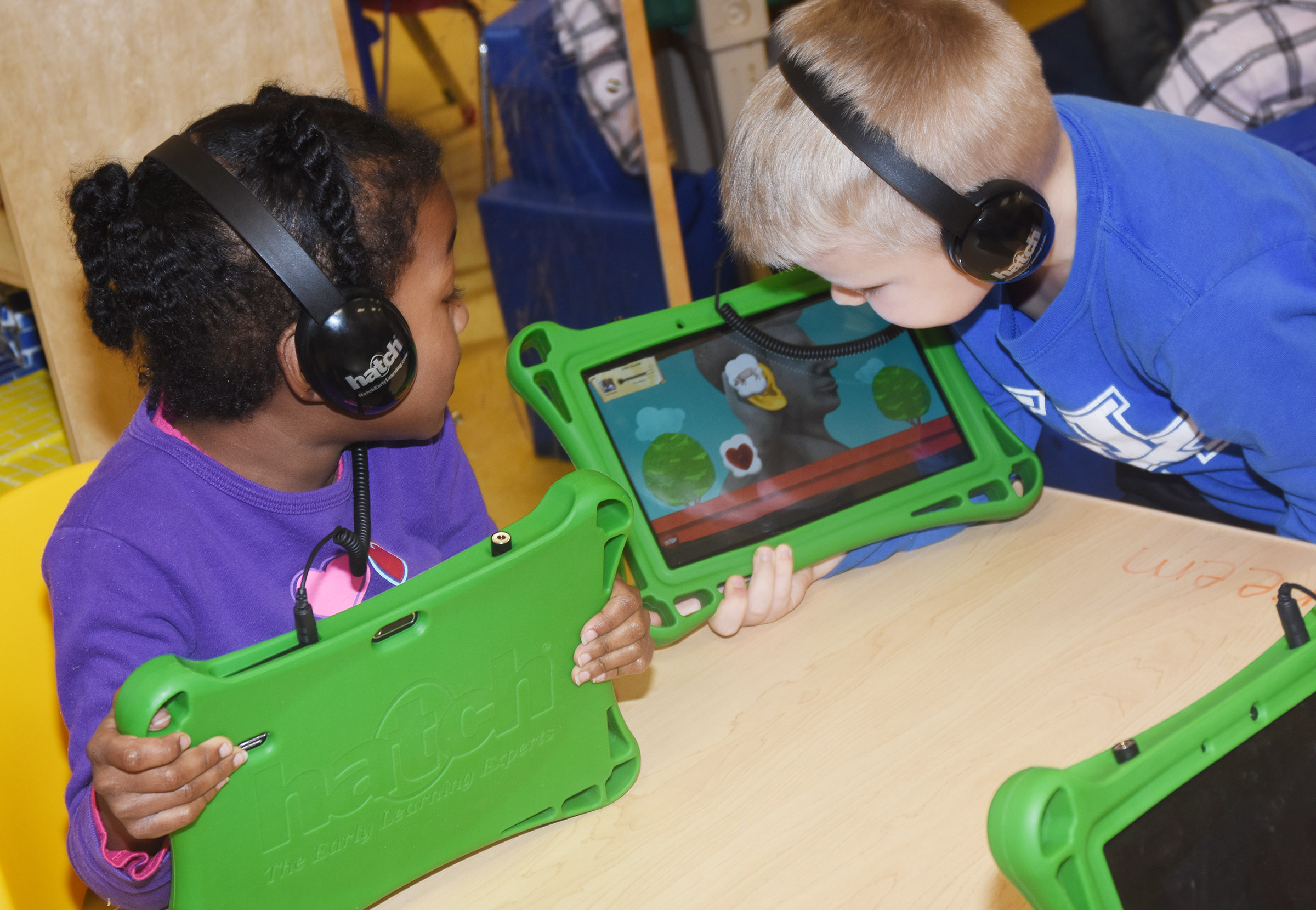 CES preschool students Priyanka Flores, at left, and Hoyt Davis watch a video on their iStartSmart tablets.