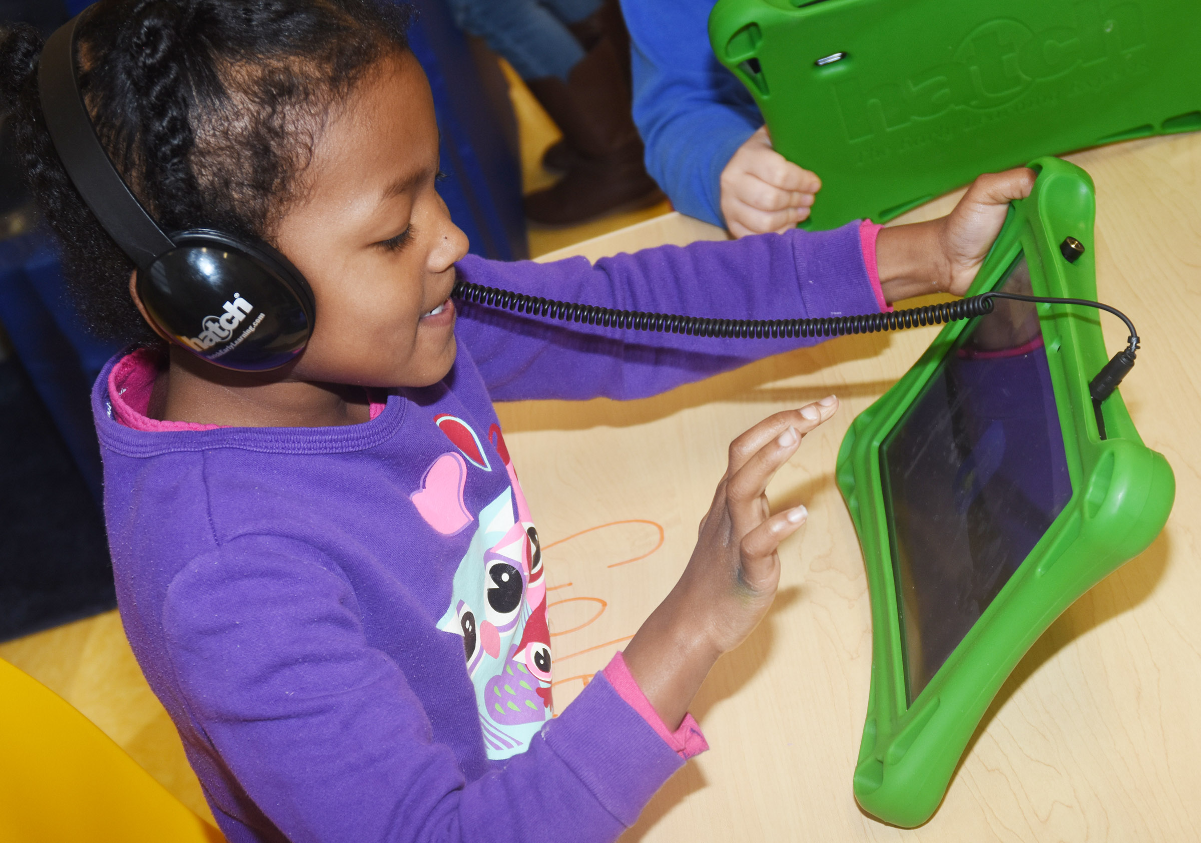 CES preschool student Priyanka Flores plays a game on her iStartSmart tablet.