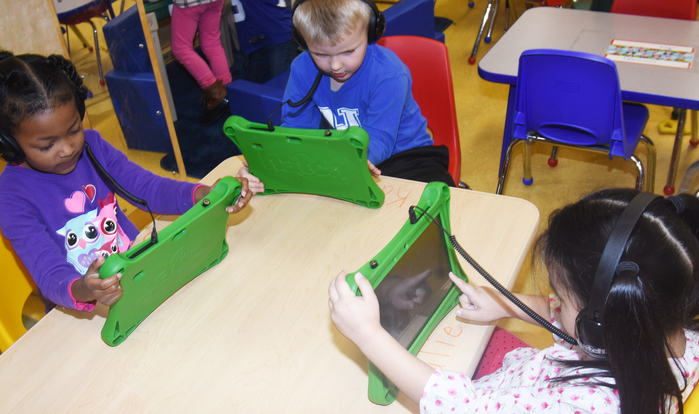 From left, CES preschool students Priyanka Flores, Hoyt Davis and Marla Bat play games on their iStartSmart tablets.