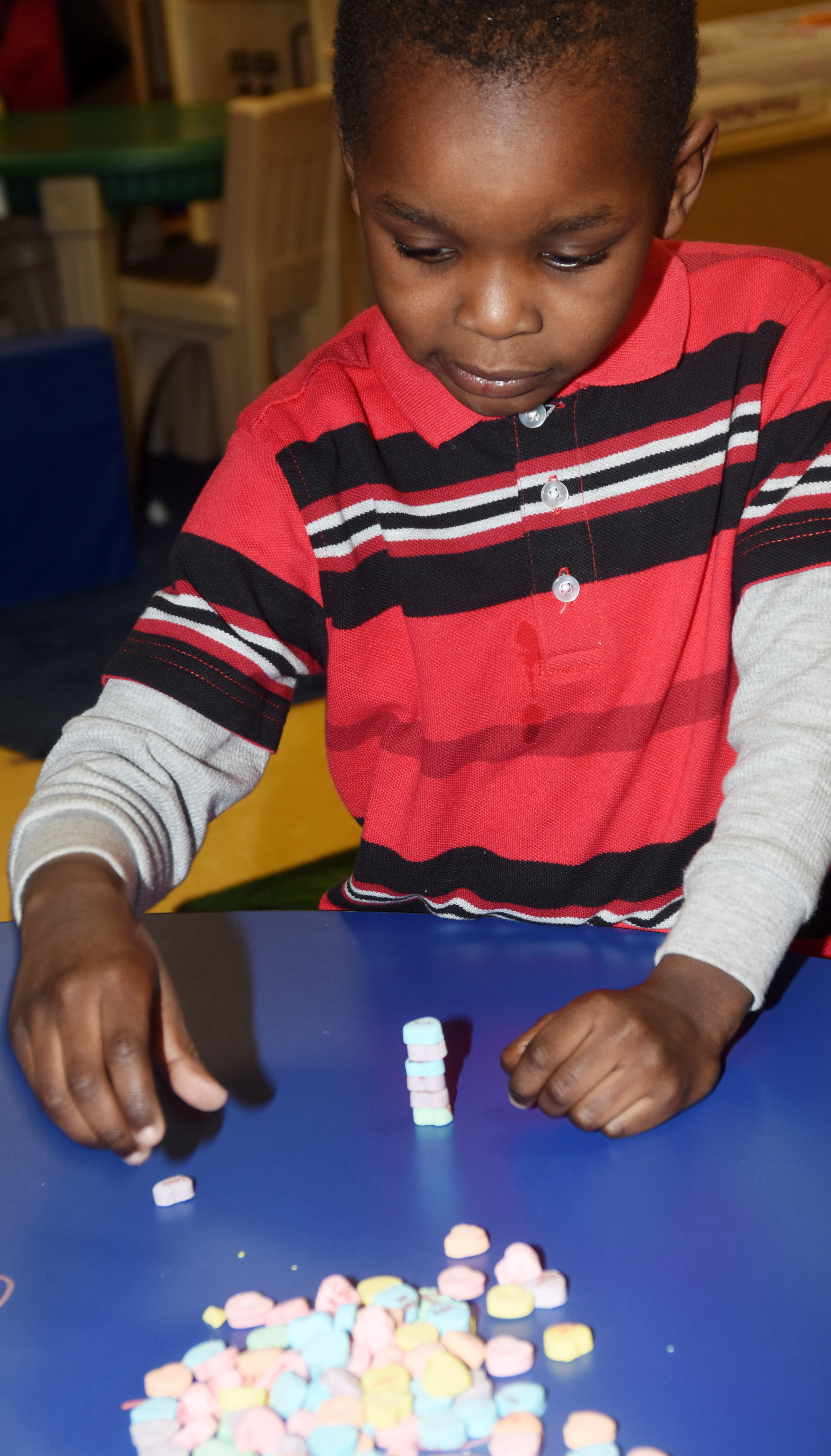 CES preschool student Xavien Smith stacks candy hearts.