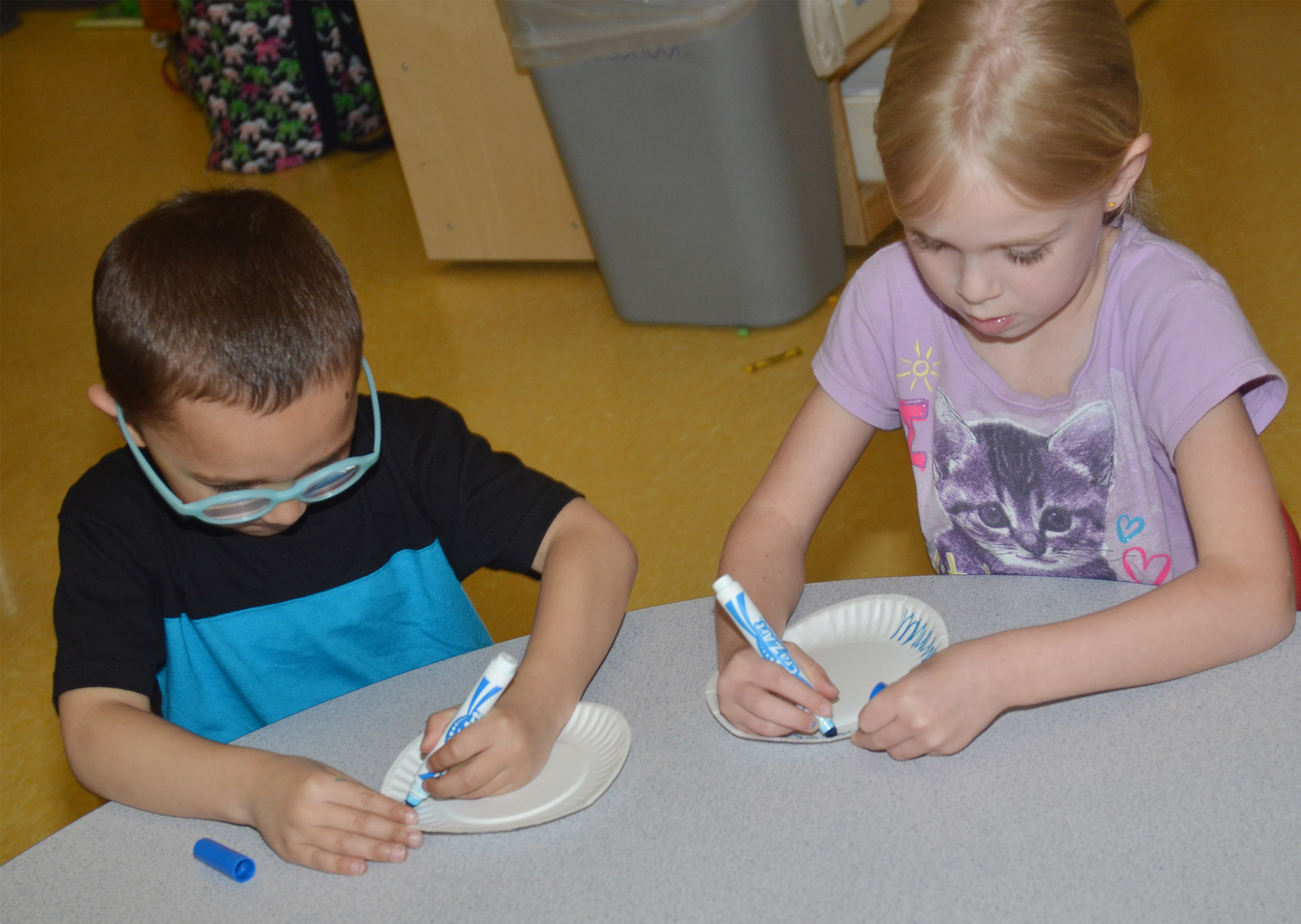 CES preschool students Chanler Mann, at left, and Alinna Bray color their paper plates, which will soon become lily pads.