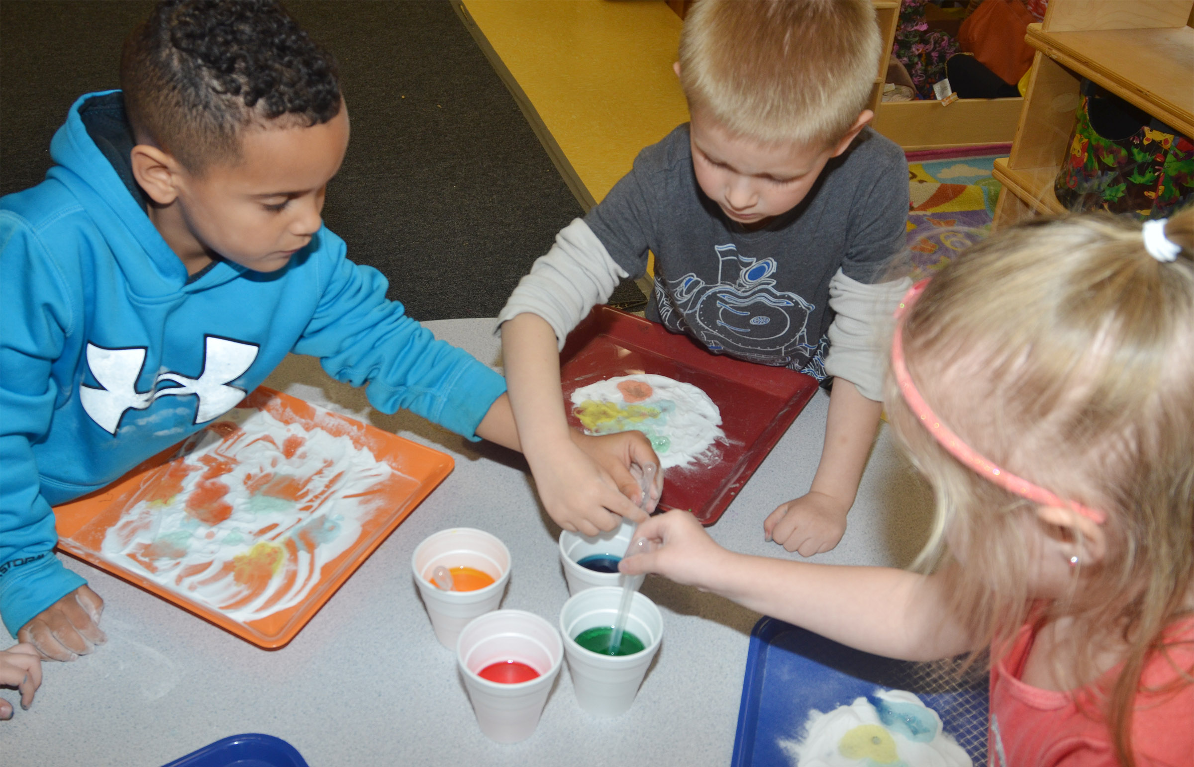 From left, CES preschool students Kingston Cowherd, Jacob Parrish and Trinity Dye add colored vinegar to baking soda to see its reaction.