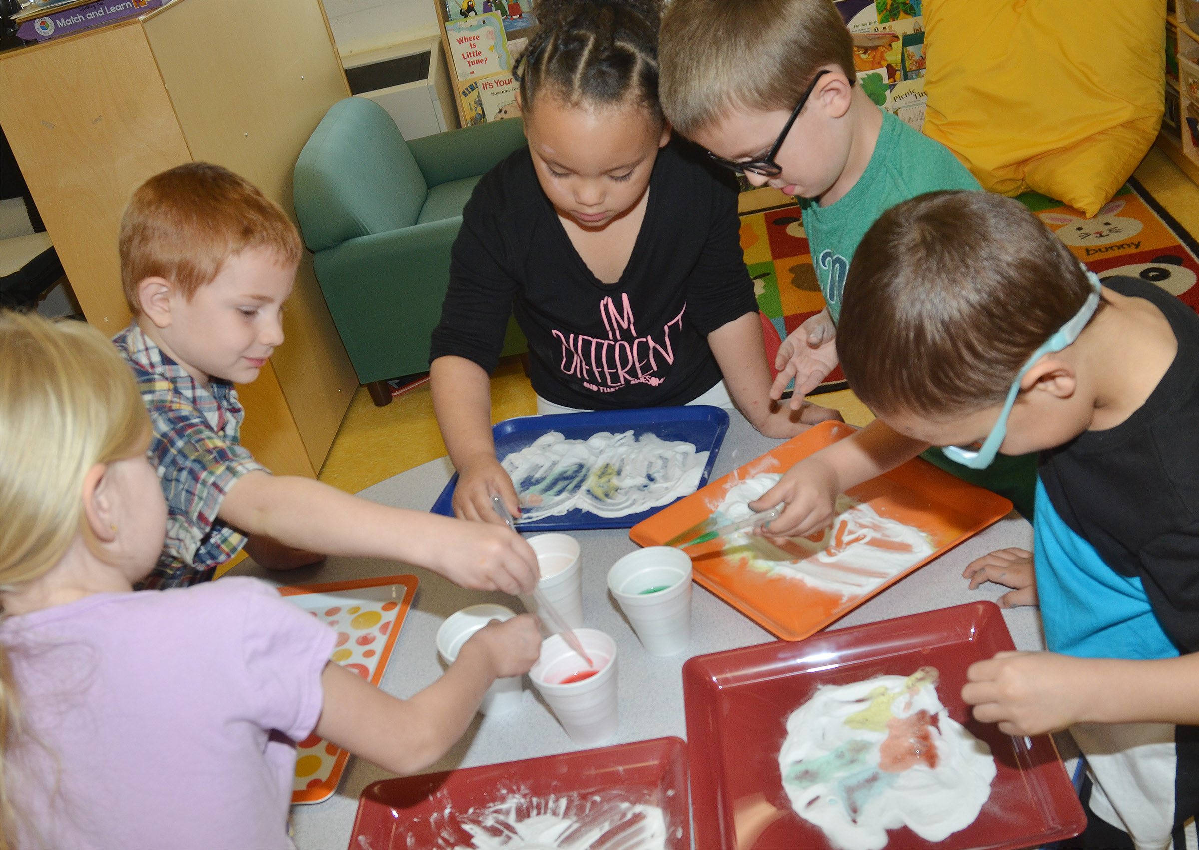 From left, CES preschool students Alinna Bray, Kennon Dotson, Lillian Merriweather, Reece Williams and Chanler Mann add colored vinegar to baking soda to see its reaction.